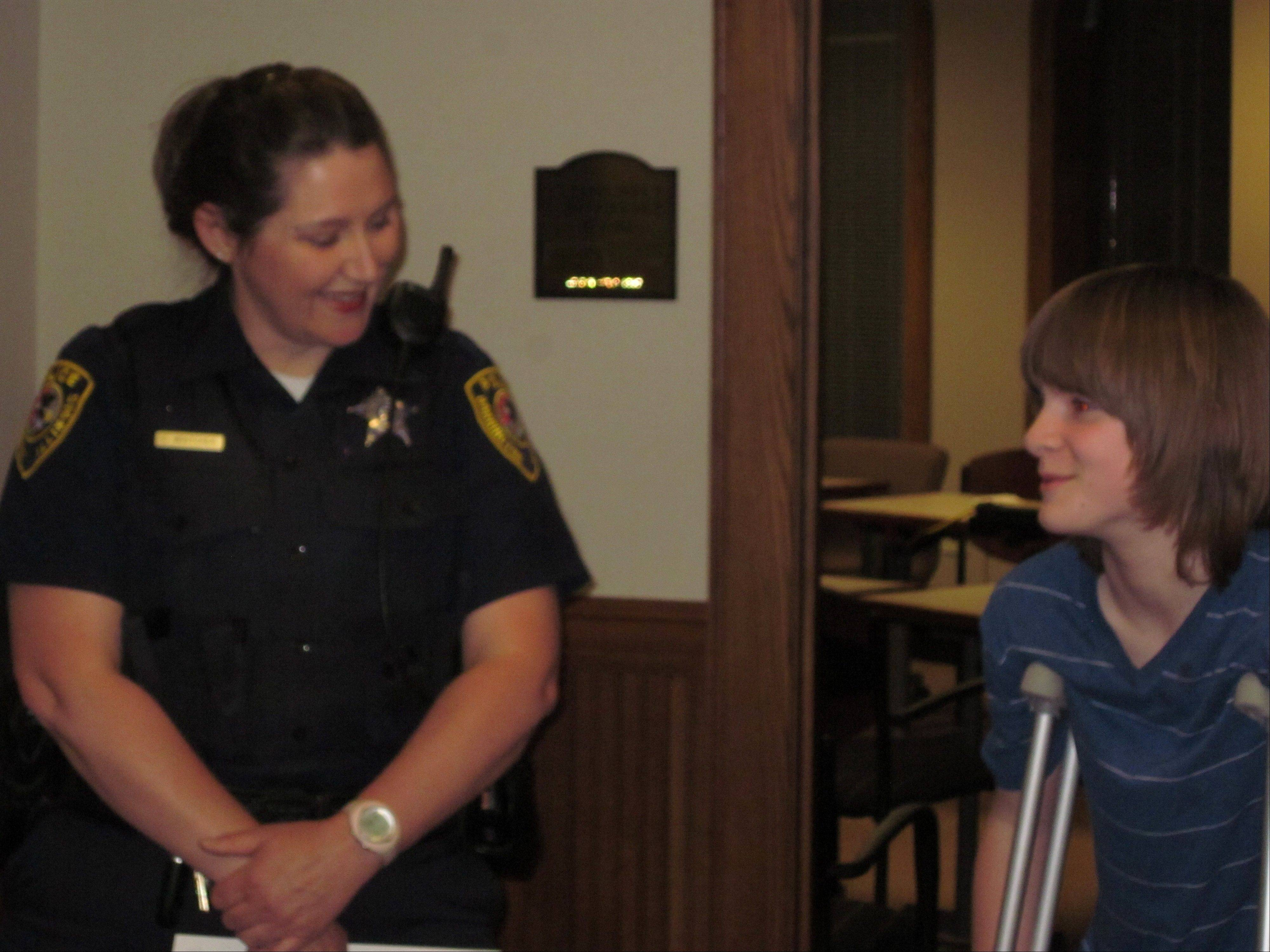 Dominic Szymanski, 11, speaks Monday night with Barrington police officer Jeniffer Whitcher, who was among the first responders who came to his aid after he was struck by a train March 15.
