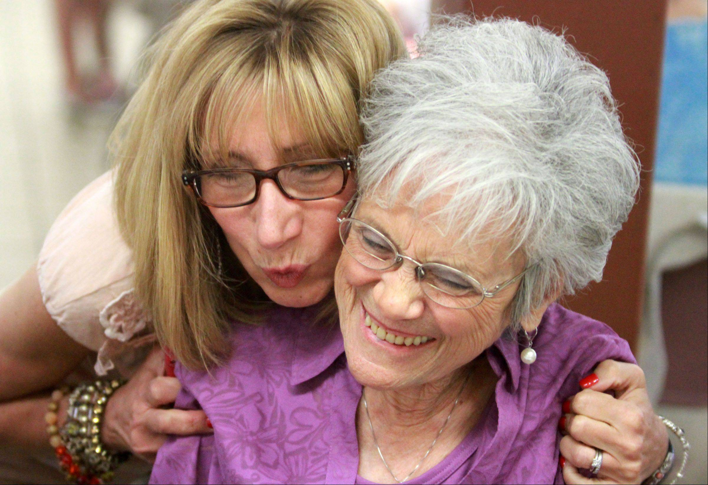 Angie Panagukos, of Hoffman Estates, gives Terri Kolbus, of Palatine, a hug, after not seeing each other since last year, as St. Theresa School in Palatine during a senior citizens luncheon and bingo Tuesday.