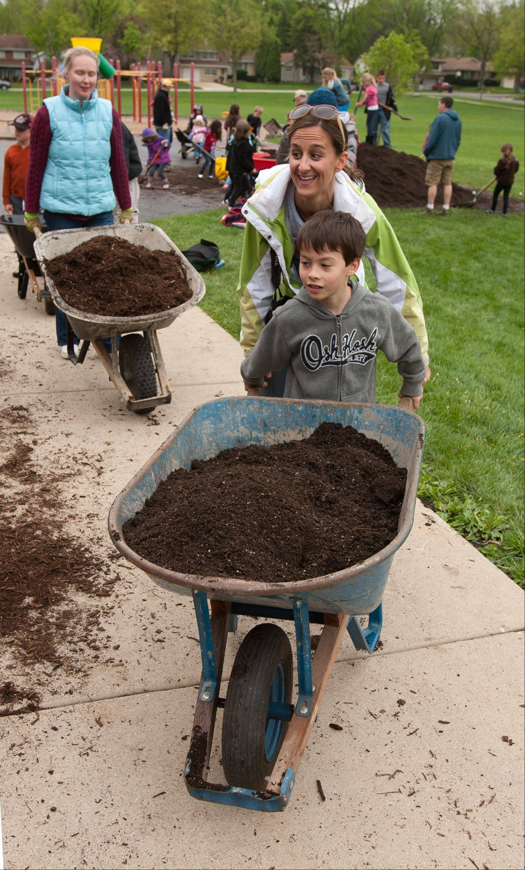 Andi Cooper and Dylan Howe, 7, of Lombard, along with other students and parents at Hammerschmidt School in Lombard, prepare garden beds for the Learn + Play gardens to be built at the school. Cooper is chairperson for Learn + Play.