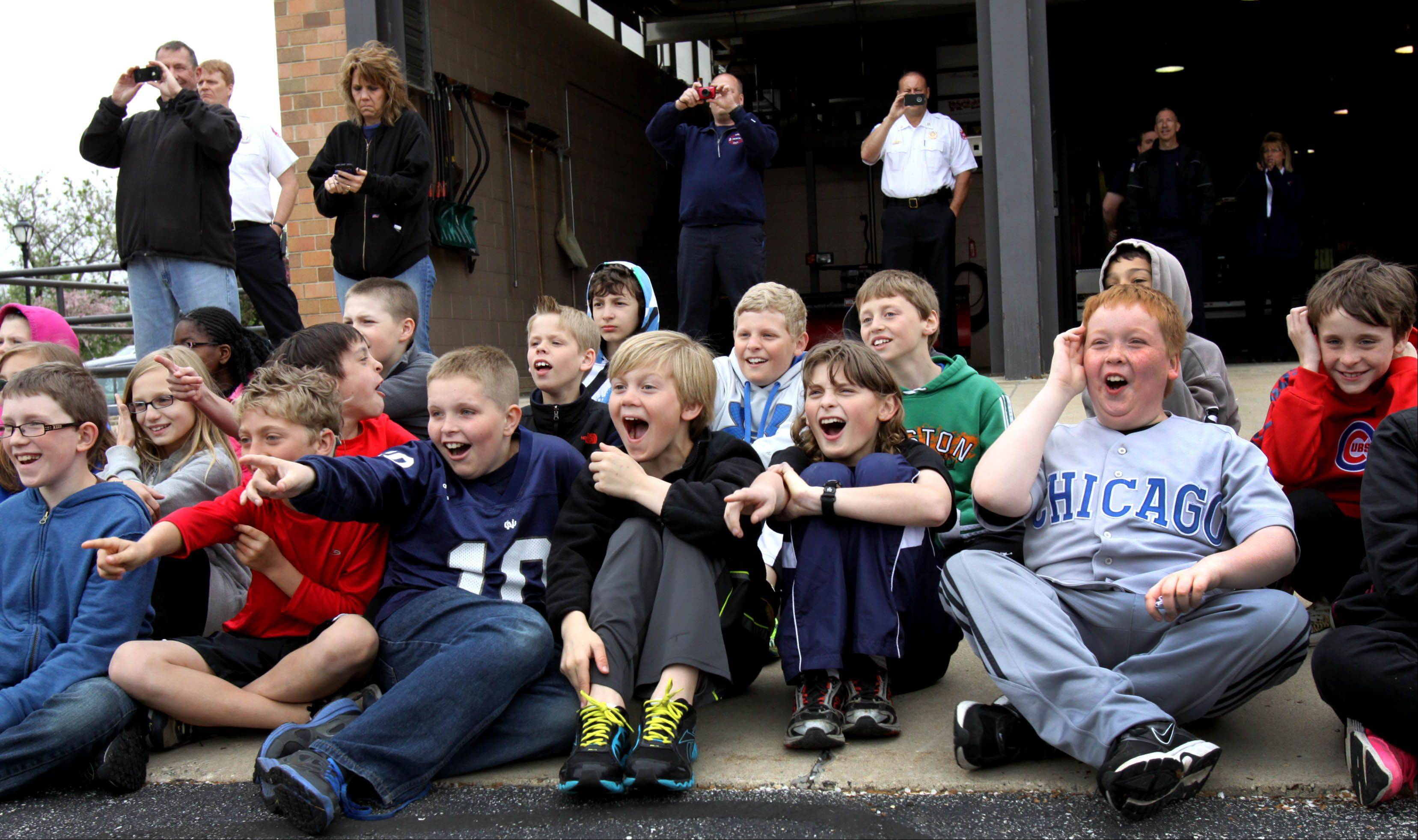 Fifth-graders from Itasca schools react as they start to see flames during a live burn demonstration by the Itasca Fire Department Friday. The demonstration was part of a tour of Itasca for the students.