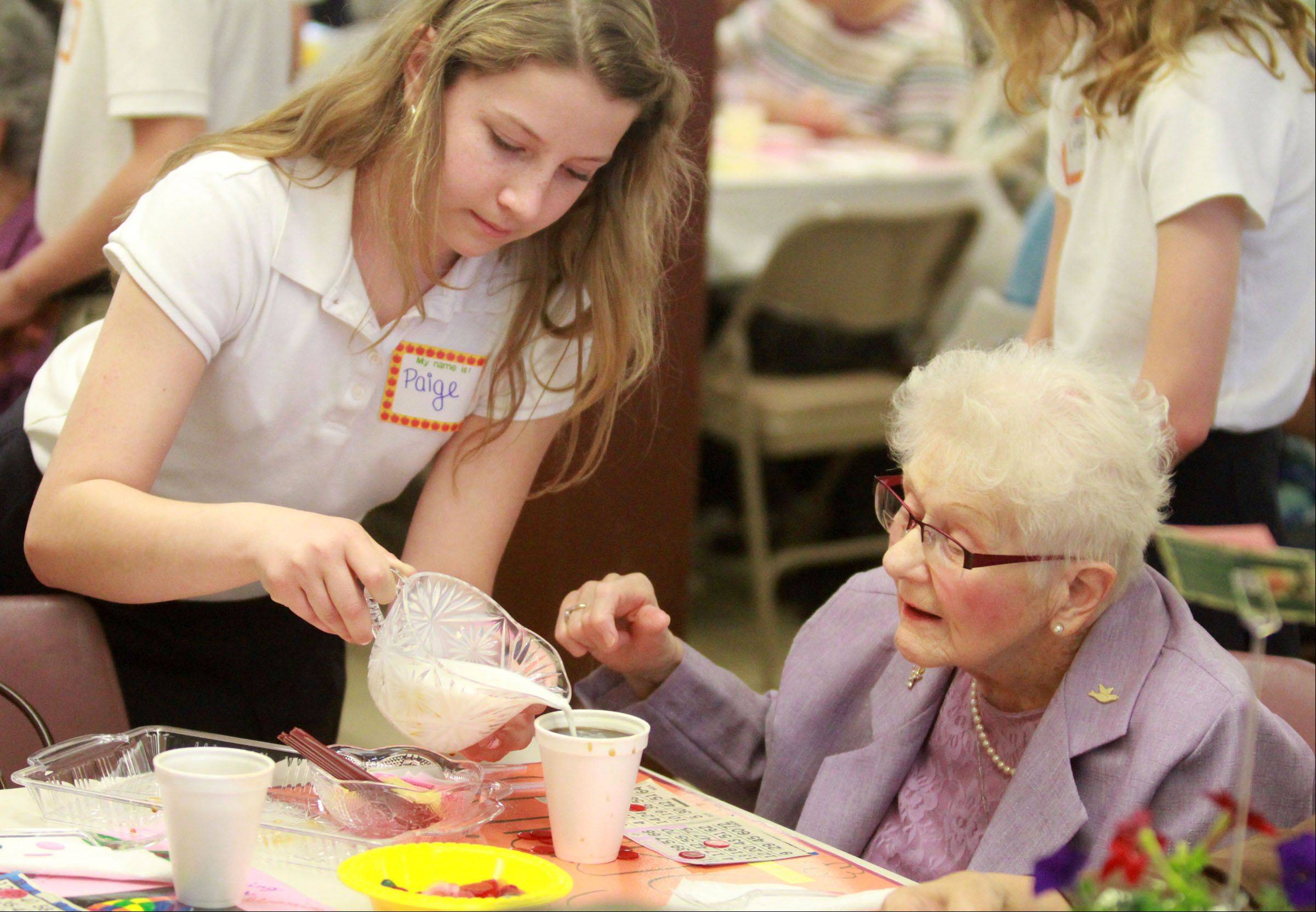 St. Theresa School sixth-grader Paige Hoadley pours cream for Lucille Ptaszek of Palatine as the school in Palatine host a senior citizens luncheon and bingo Tuesday.