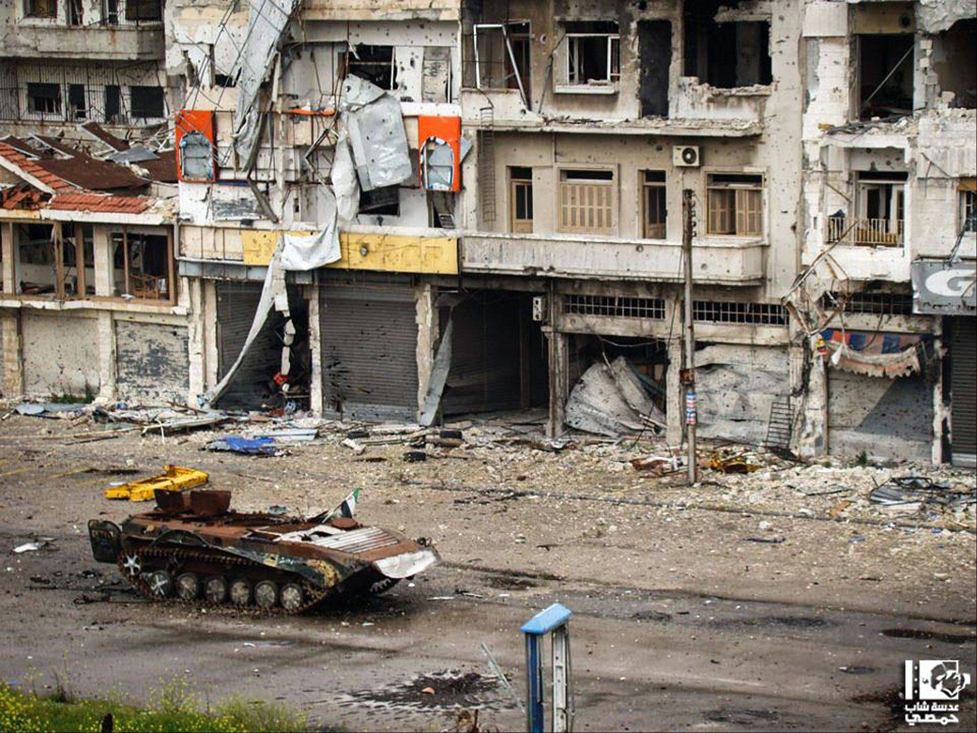 A destroyed Syrian tank is seen at al-Qossur neighborhood in Homs province, Syria, Monday. Syrian troops have taken full control of a town near the highway linking the capital Damascus with Jordan, a new advance in the regime's campaign to drive rebels from the strategic south, an activist group said Monday.