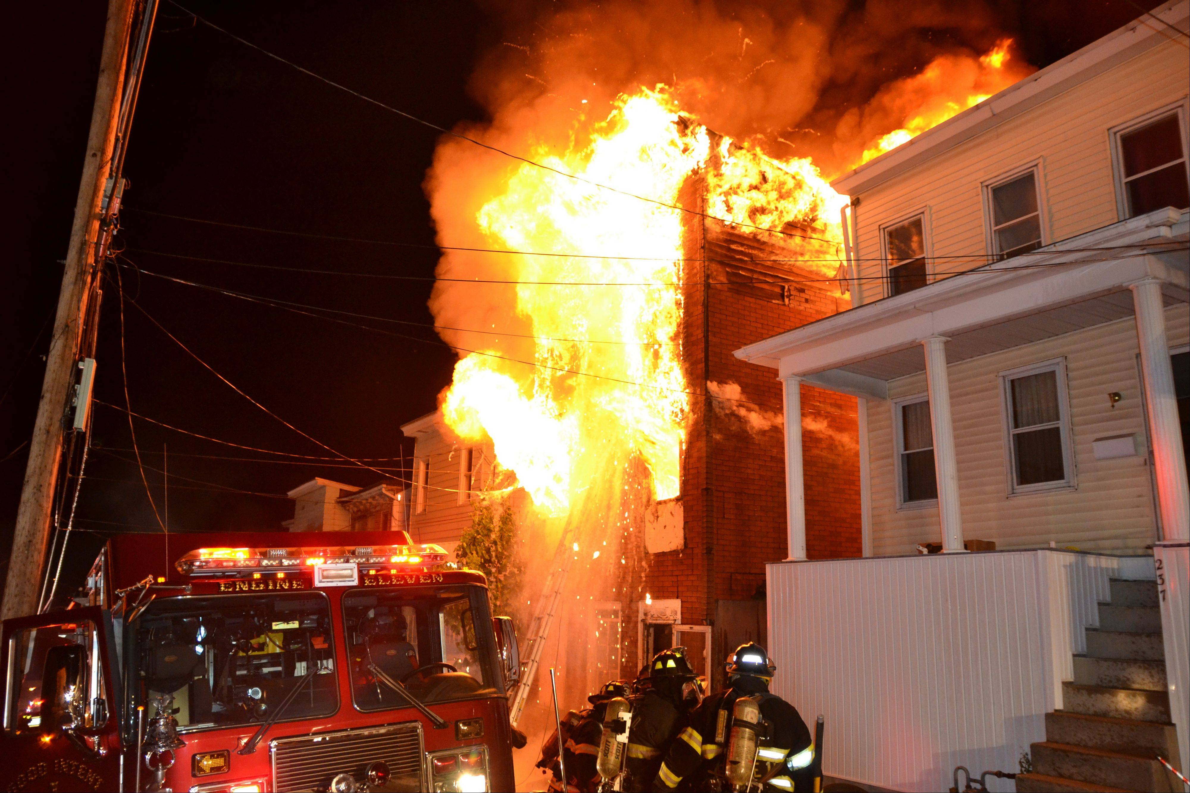 Firefighters battle an early-morning house fire that killed four children and two adults in Pottsville, Pa., Monday. The blaze broke out around 11:55 p.m. Sunday at the single-family home.