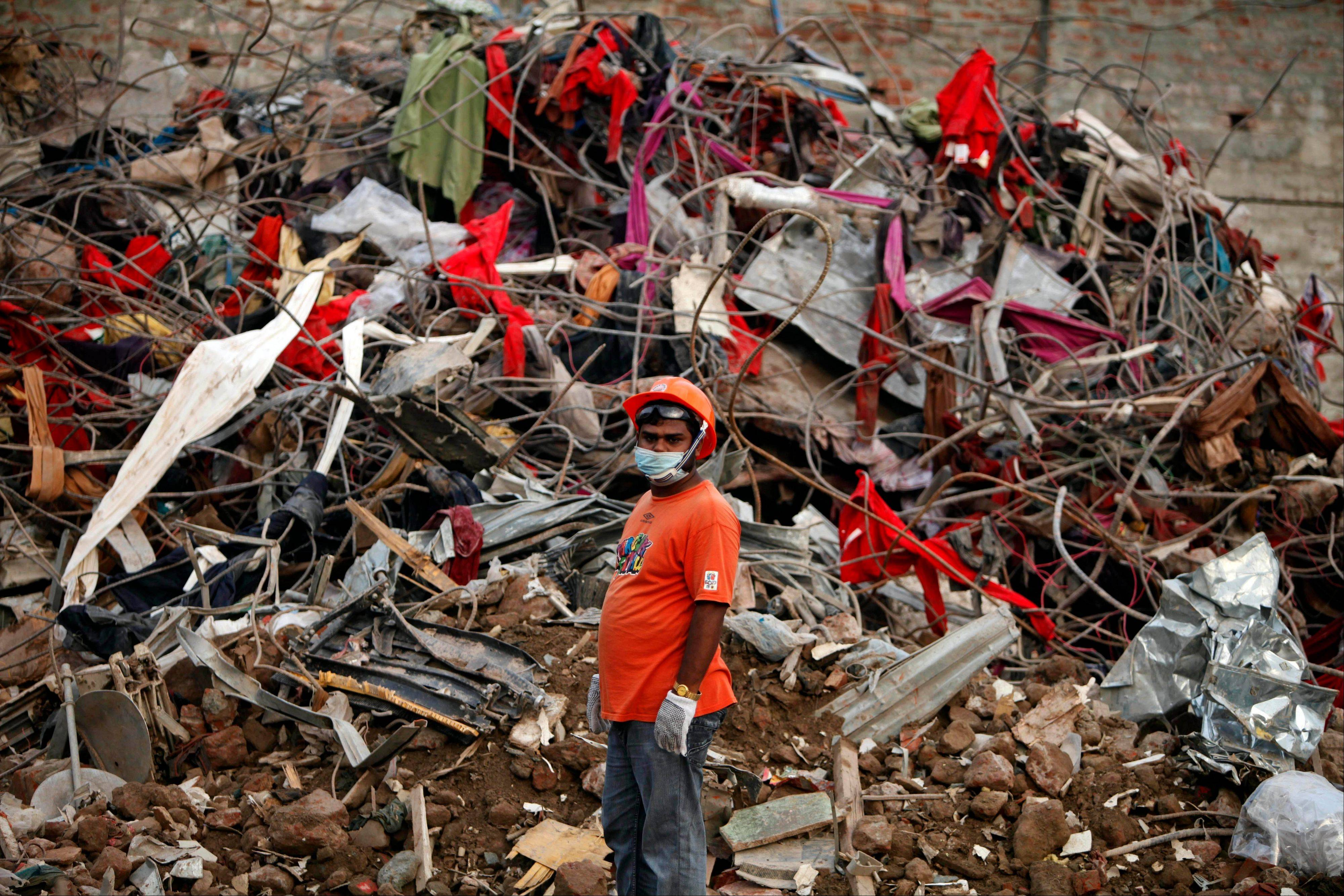 A Bangladeshi rescuer stands amid the rubble of a garment factory building that collapsed on April 24 as they continue searching for bodies in Savar, near Dhaka, Bangladesh, Sunday. As of Monday, the search for the dead is over.
