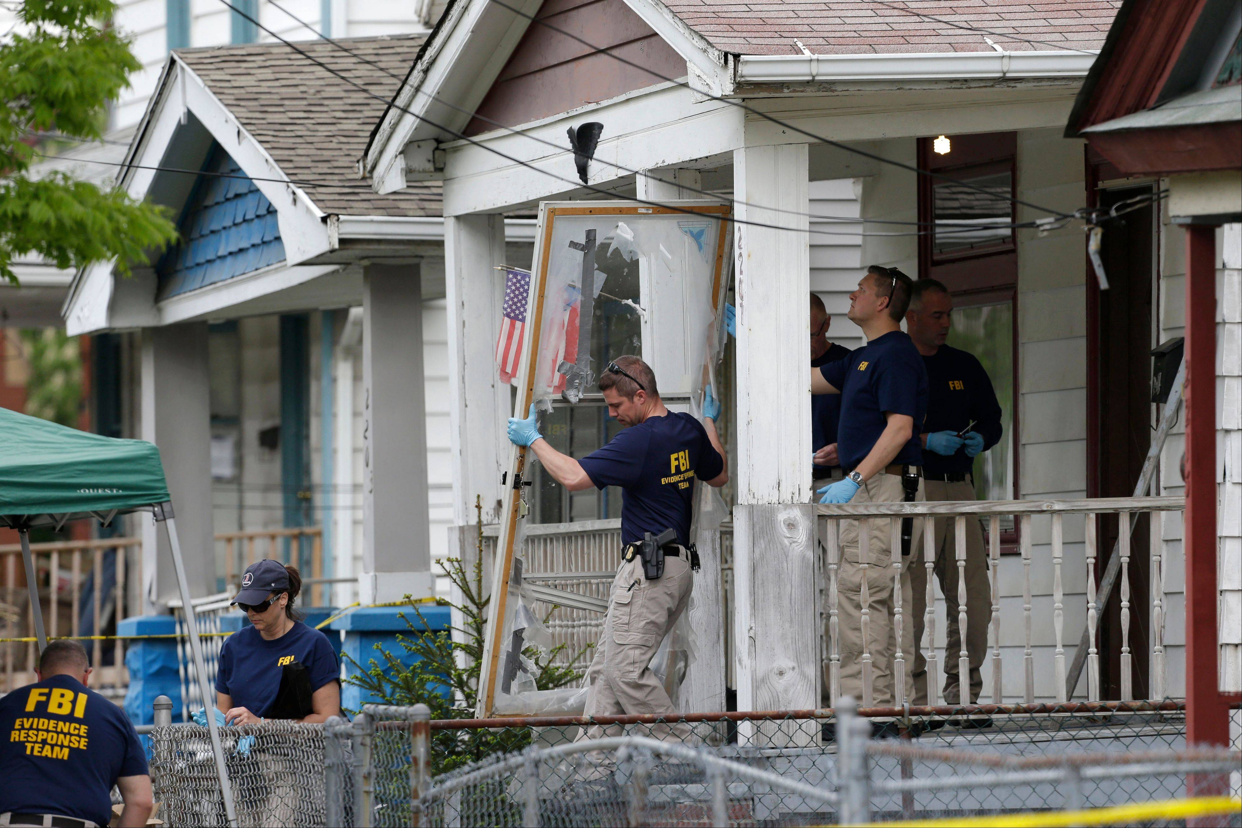 Members of the FBI evidence response team carry out the front screen door from the house where three women were held captive in Cleveland. Cleveland officials are trying to keep the house intact until the trial of the women's suspected abductor is concluded.