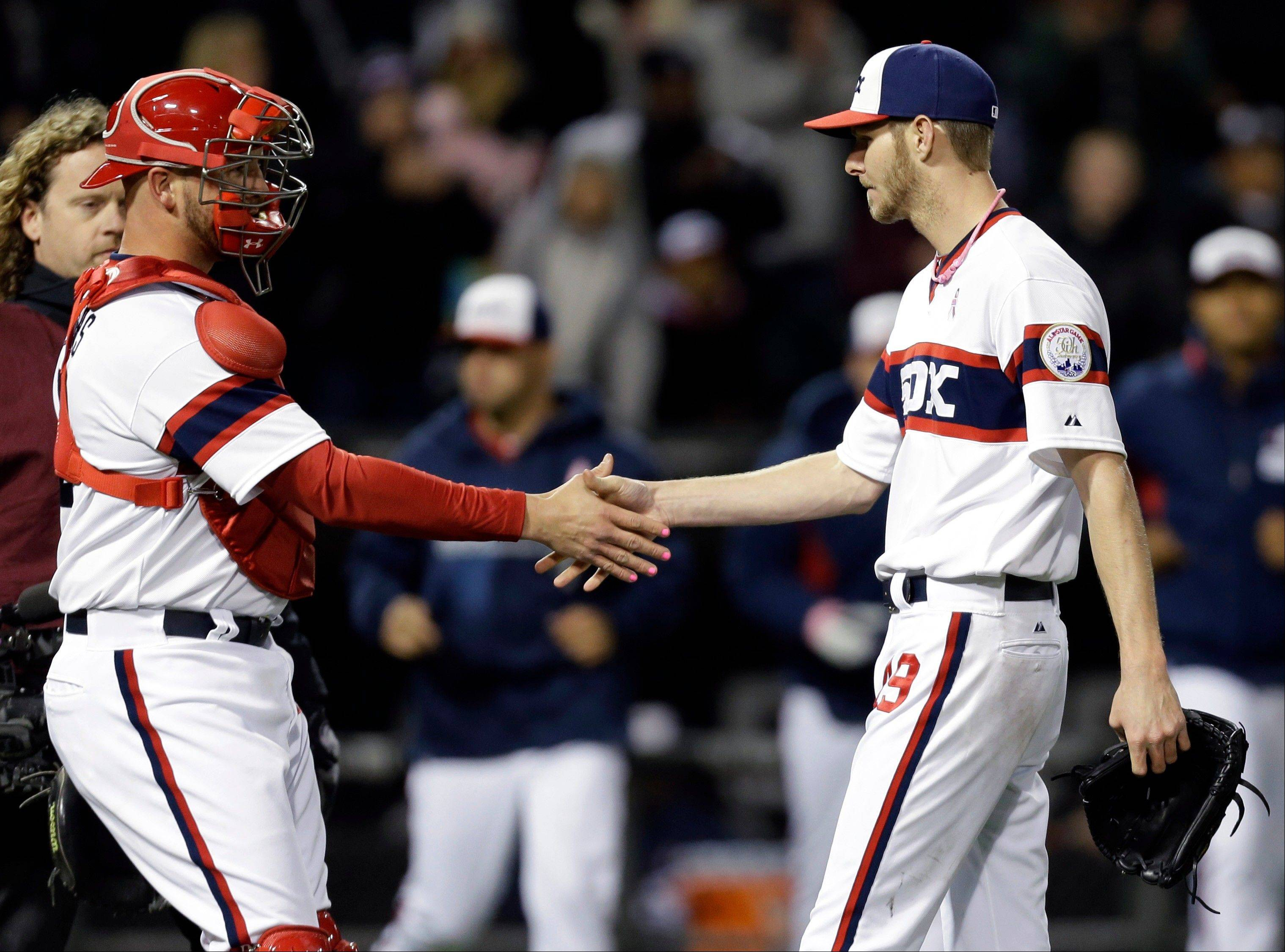 Chicago White Sox starter Chris Sale, right, celebrates with catcher Tyler Flowers after the White Sox defeated the Los Angeles Angels 3-0 in a baseball game Sunday in Chicago. Sale pitched the first complete shutout of his career Sunday night, a 1-hit gem over the Angels. Alexei Ramirez's clutch 2-run single in the seventh inning also helped spark the White Sox to a 3-0 win.