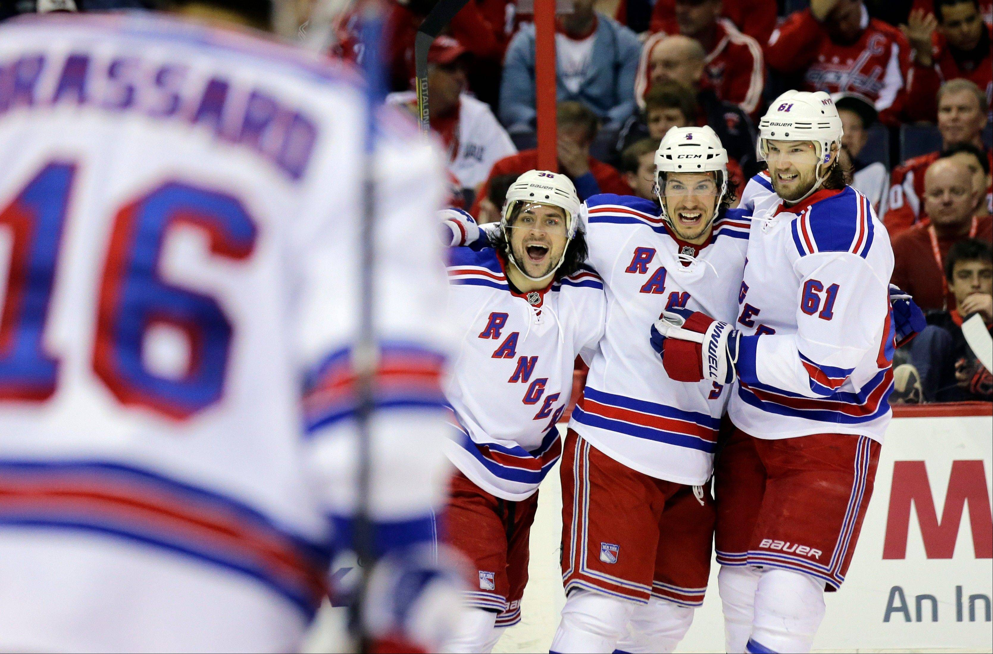 New York Rangers right wing Mats Zuccarello (36), defenseman Michael Del Zotto (4), and left wing Rick Nash (61) celebrate Del Zotto's goal in the second period, of Game 7 first-round NHL Stanley Cup playoff hockey series against the Washington Capitals, Monday, May 13, 2013 in Washington.