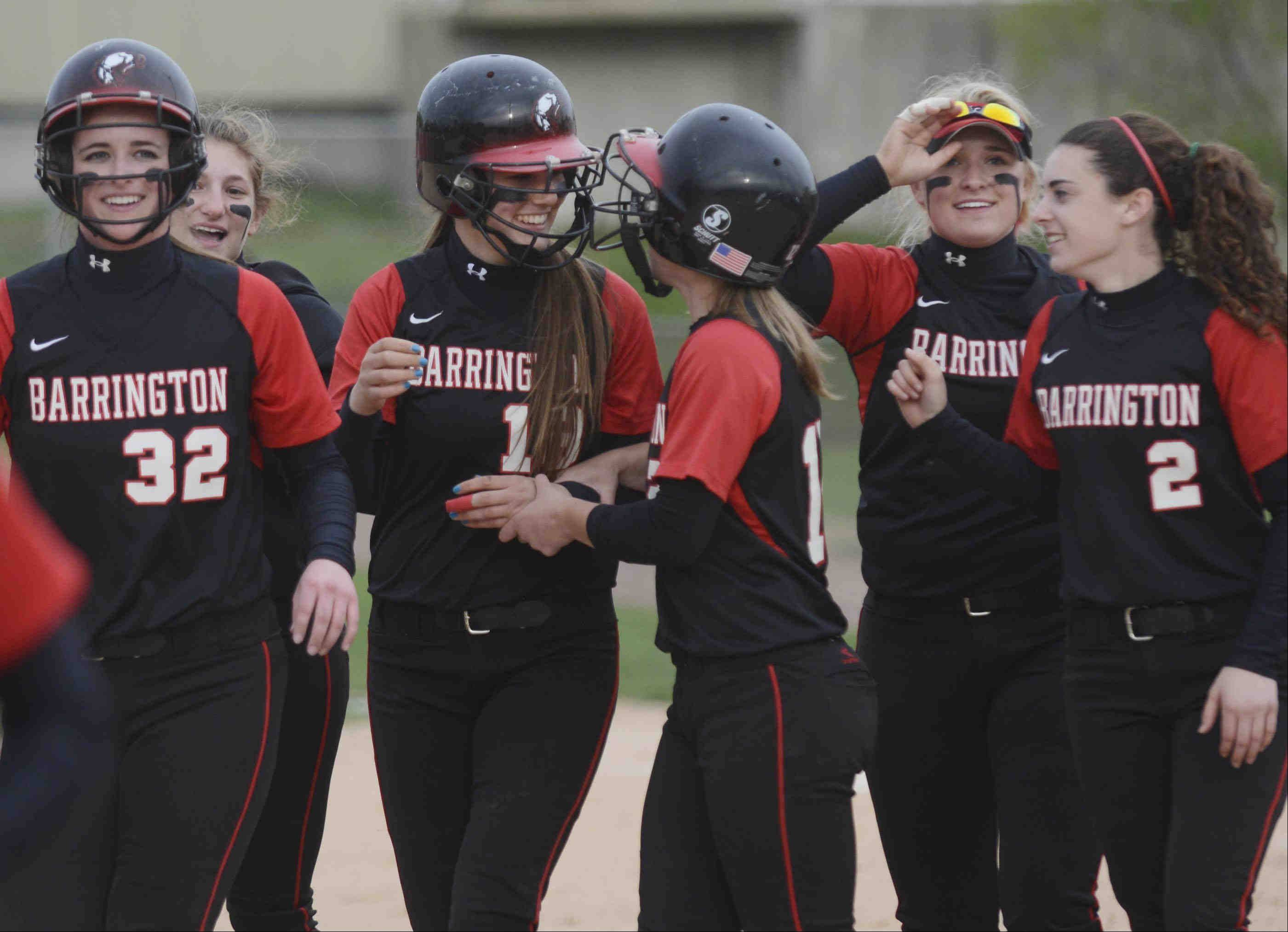 Barrington's Katie Dehnert, middle, is surrounded by smiling teammates after her two-out, bases-loaded groundball drove in the winning run Monday at the Fields of Dreams in Barrington. Barrington completed a perfect run against the Mid-Suburban League with a 1-0 victory.