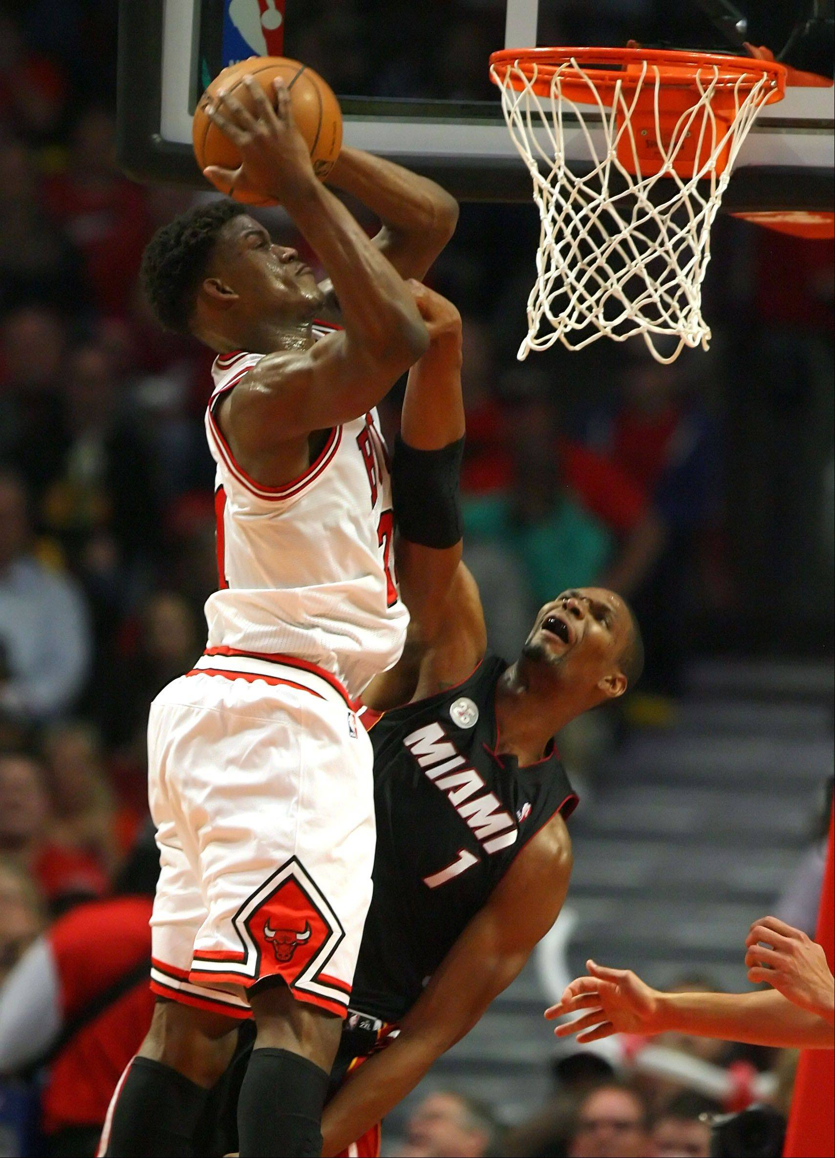Chicago Bulls small forward Jimmy Butler goes for a rebound with Miami Heat center Chris Bosh .