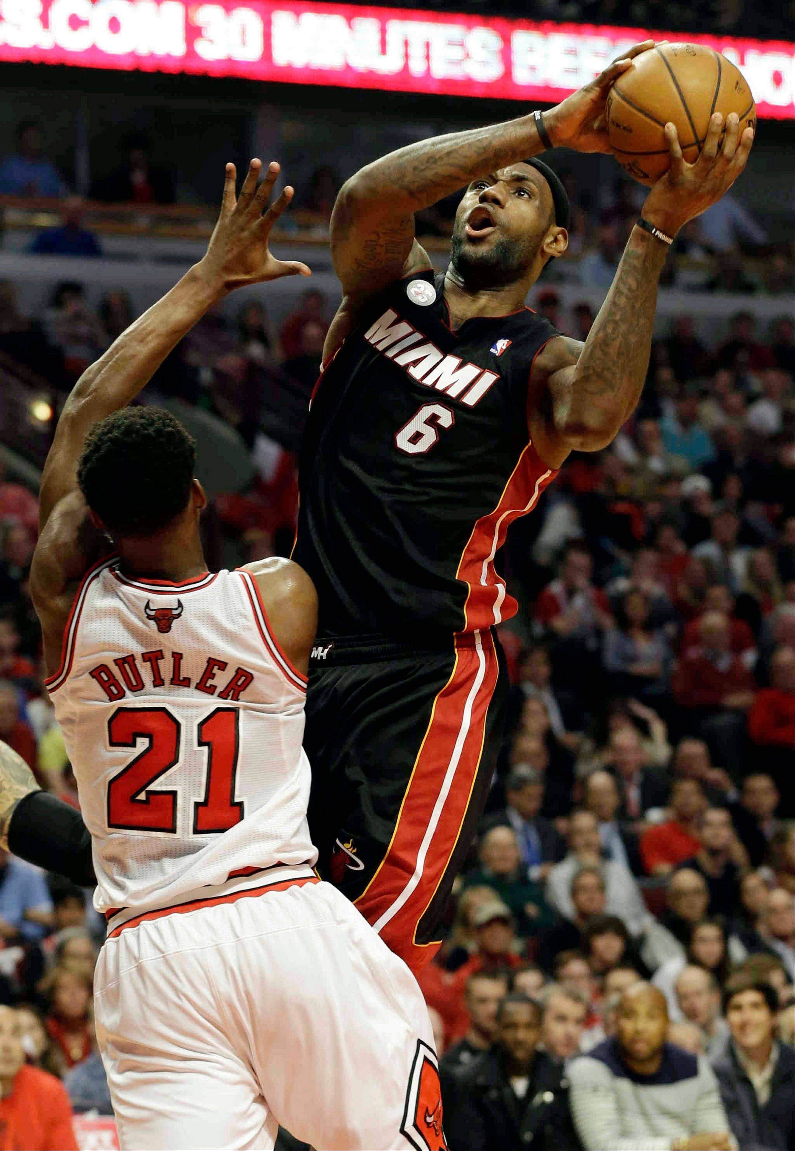 Miami Heat forward LeBron James goes up for a shot against Bulls forward Jimmy Butler during the first half of Game 4 of an NBA basketball playoffs Eastern Conference semifinal on Monday, May 13, 2013, in Chicago.