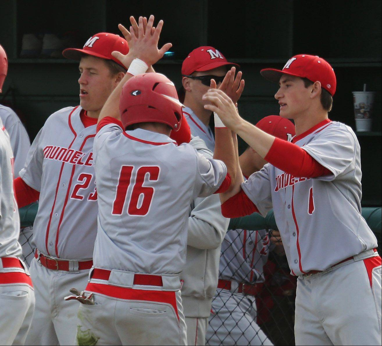Mundelein player Mike Metz is congratulated by teammates after scoring the Mustangs' second run Monday against Stevenson.