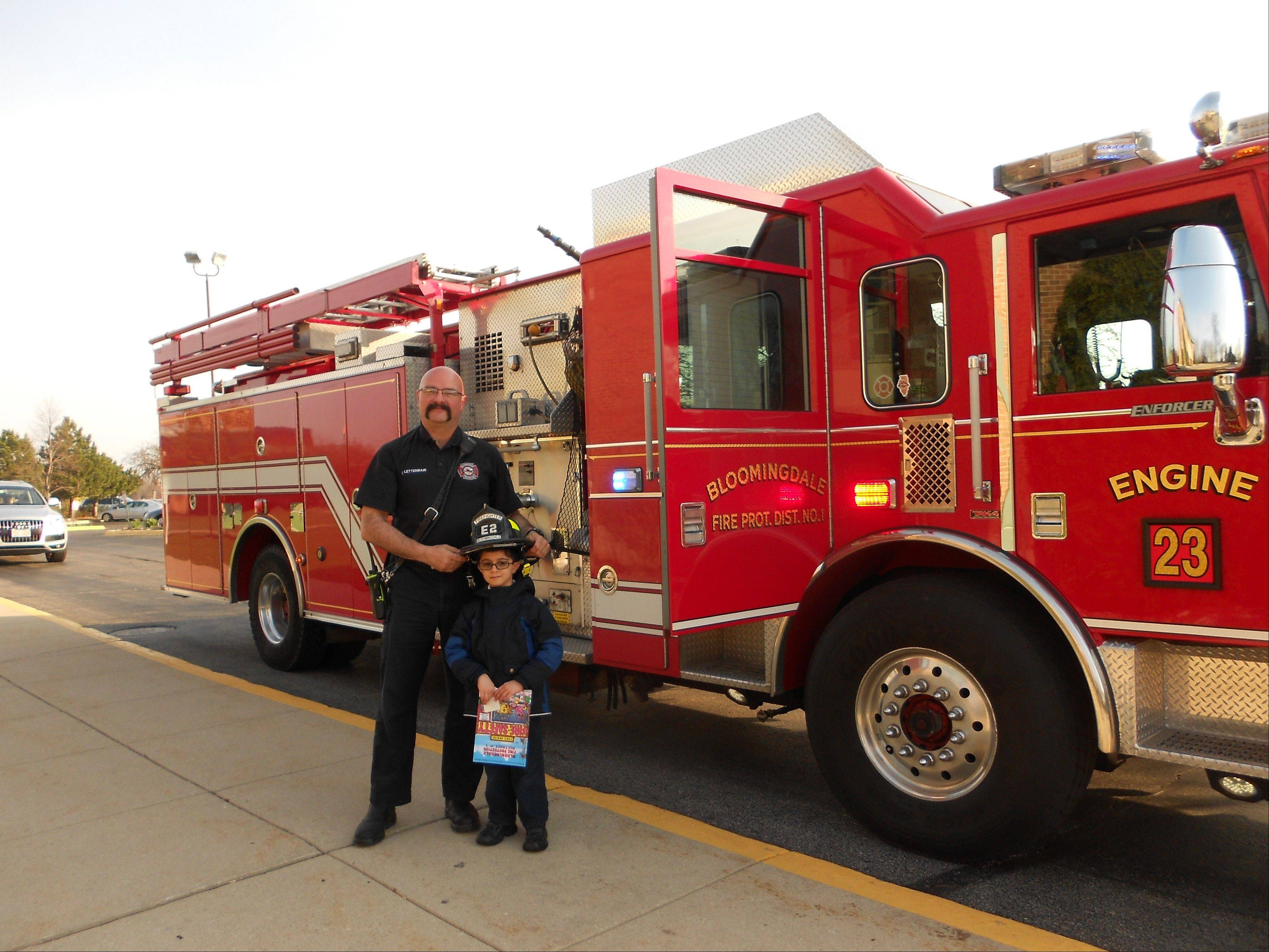 Kindergartner Rayhaan Irani of Carol Stream got a ride to school in a Bloomingdale Fire Protection District engine with Lt. Lou Lettenmair and several firefighters. Rayhaan's parents won the opportunity in an auction fundraiser for St. Isidore School.