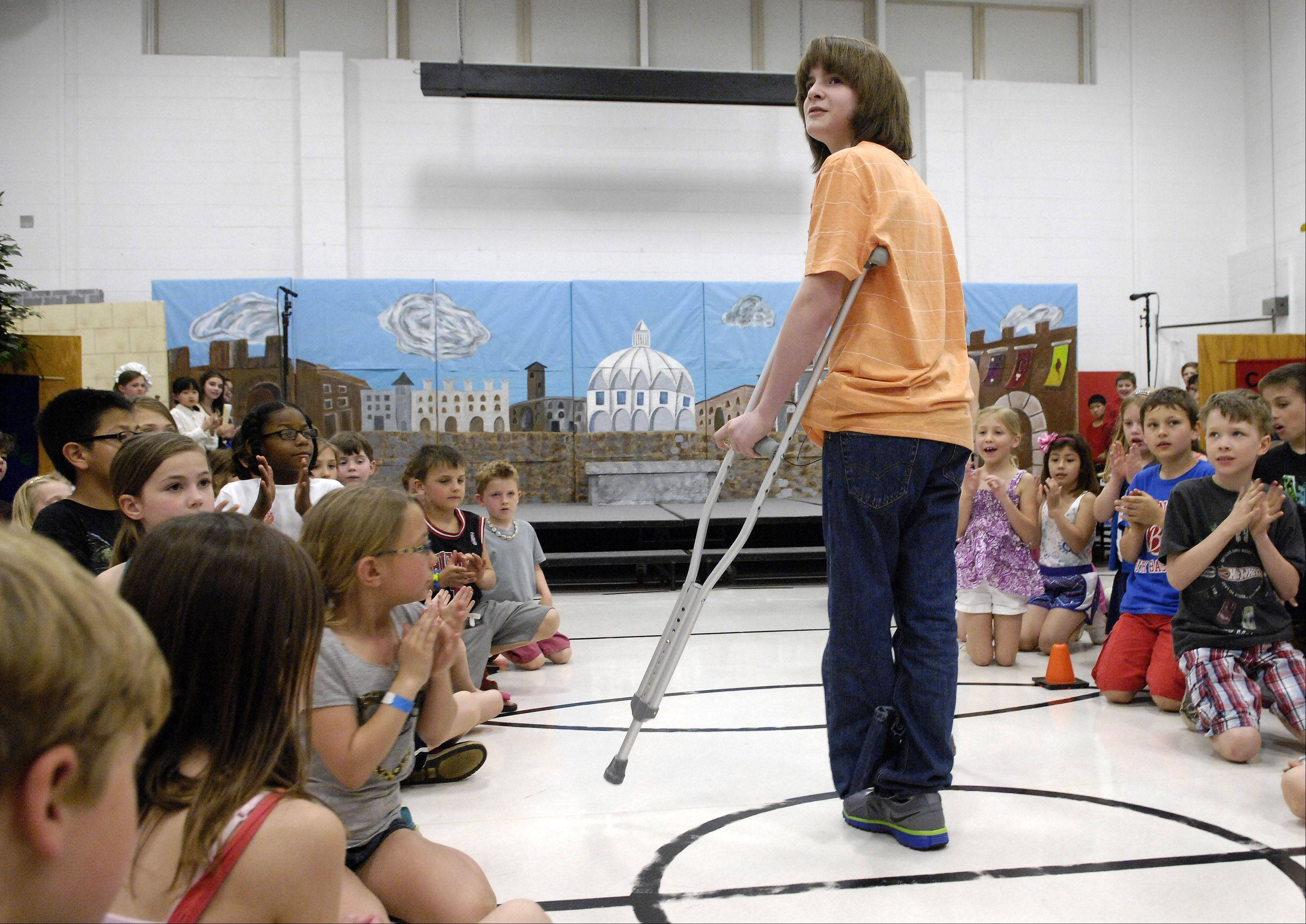 Dominic Szymanski, 11, basks in the cheers of his classmates as he made a surprise visit to Hough Street School in Barrington Tuesday, his first day back after being hit by a train in March.