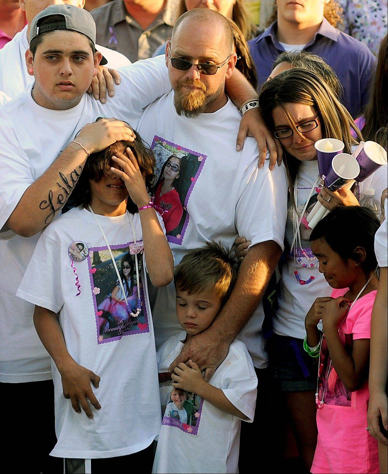 The family of slain 8-year-old girl Leila Fowler. Leila's father, Barney Fowler, center, stands with Leila's mother Crystal Walters, right, at his shoulder. Fowler says he believes 12-year-old son, who was arrested in the stabbing death of his 8-year-old sister, is innocent until he is shown evidence that proves otherwise.
