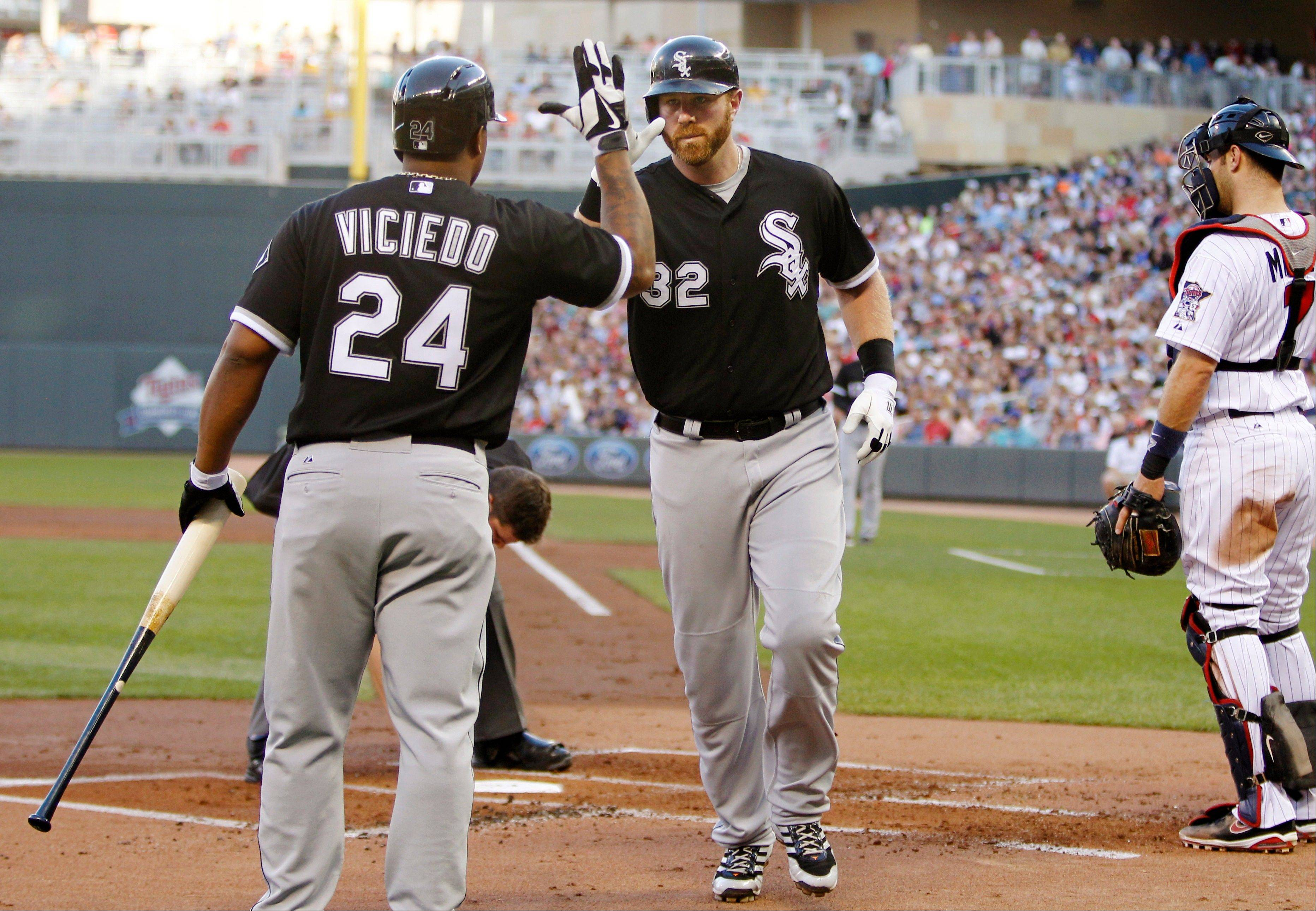 Adam Dunn (32) is congratulated by Dayan Viciedo (24) after hitting a solo home run against Minnesota Twins starting pitcher Kevin Correia during the second inning of a baseball game, Tuesday, May 14, 2013, in Minneapolis. (AP Photo/Genevieve Ross)