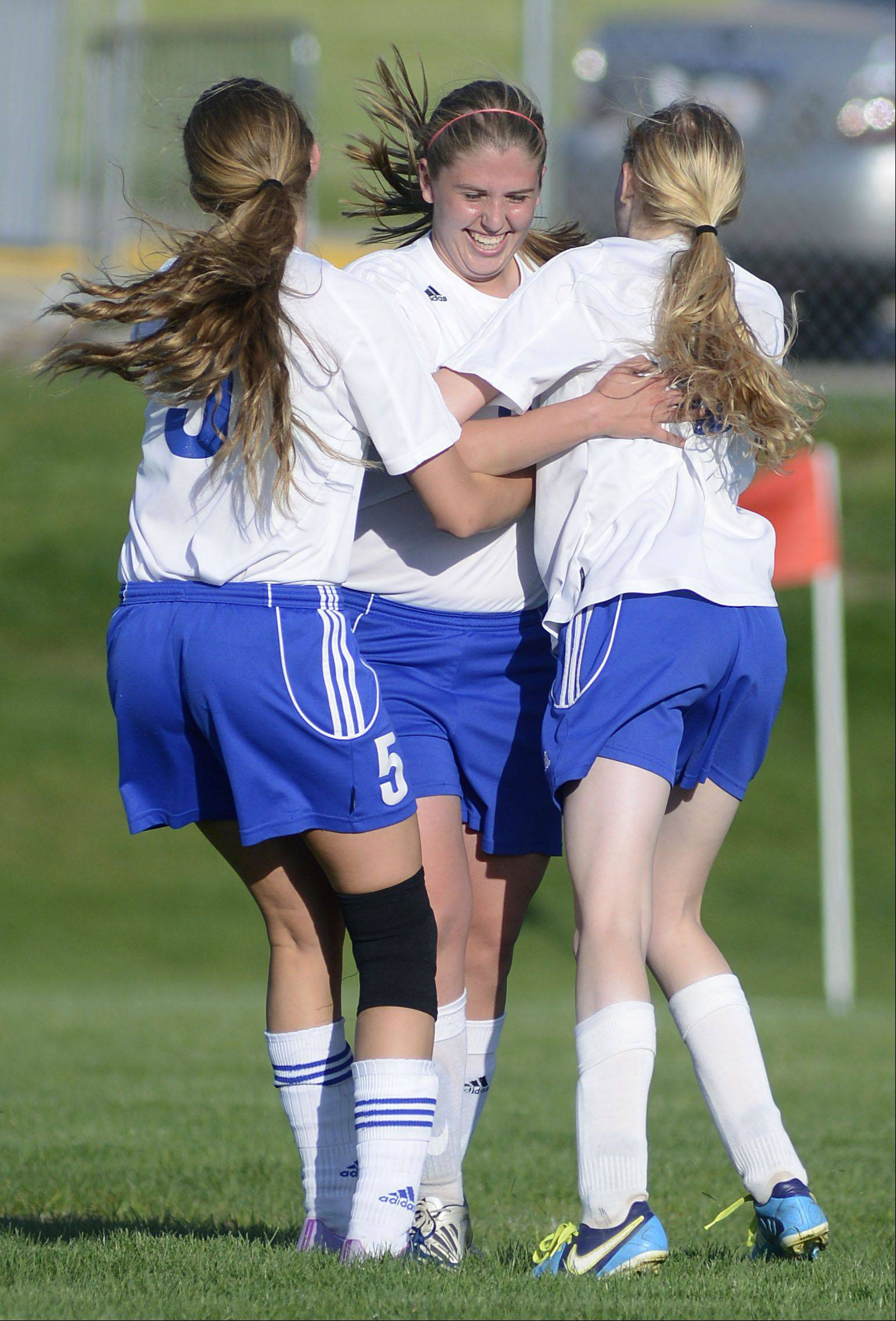 Burlington Central�s Ellen Jayne, left, Alyssa Messina, center, and Cali Andrew embrace after tying the score with Hampshire in the second half of the Class 2A regional semifinal on Tuesday.