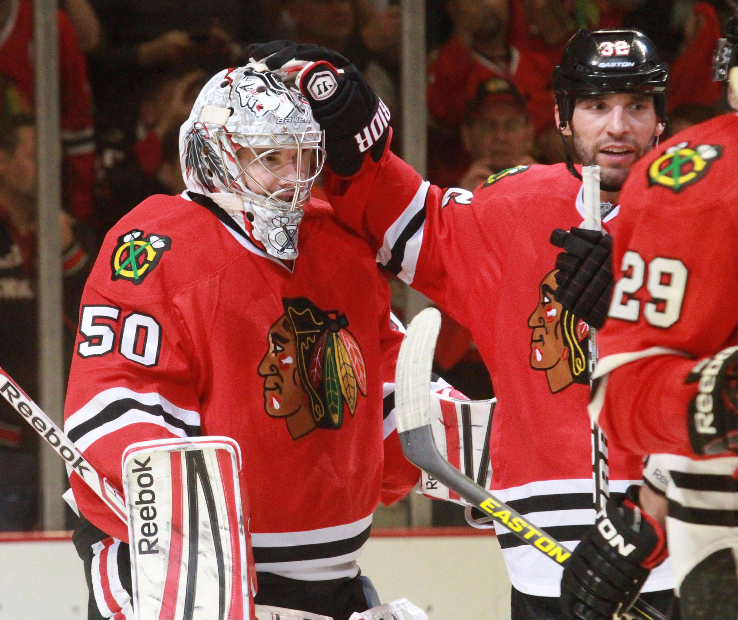 Chicago Blackhawks defenseman Michal Rozsival gives goalie Corey Crawford a hand after winning 5-1 against Minnesota Wild in game 5 of the NHL Western Conference first-round playoff series at the United Center in Chicago on Thursday.