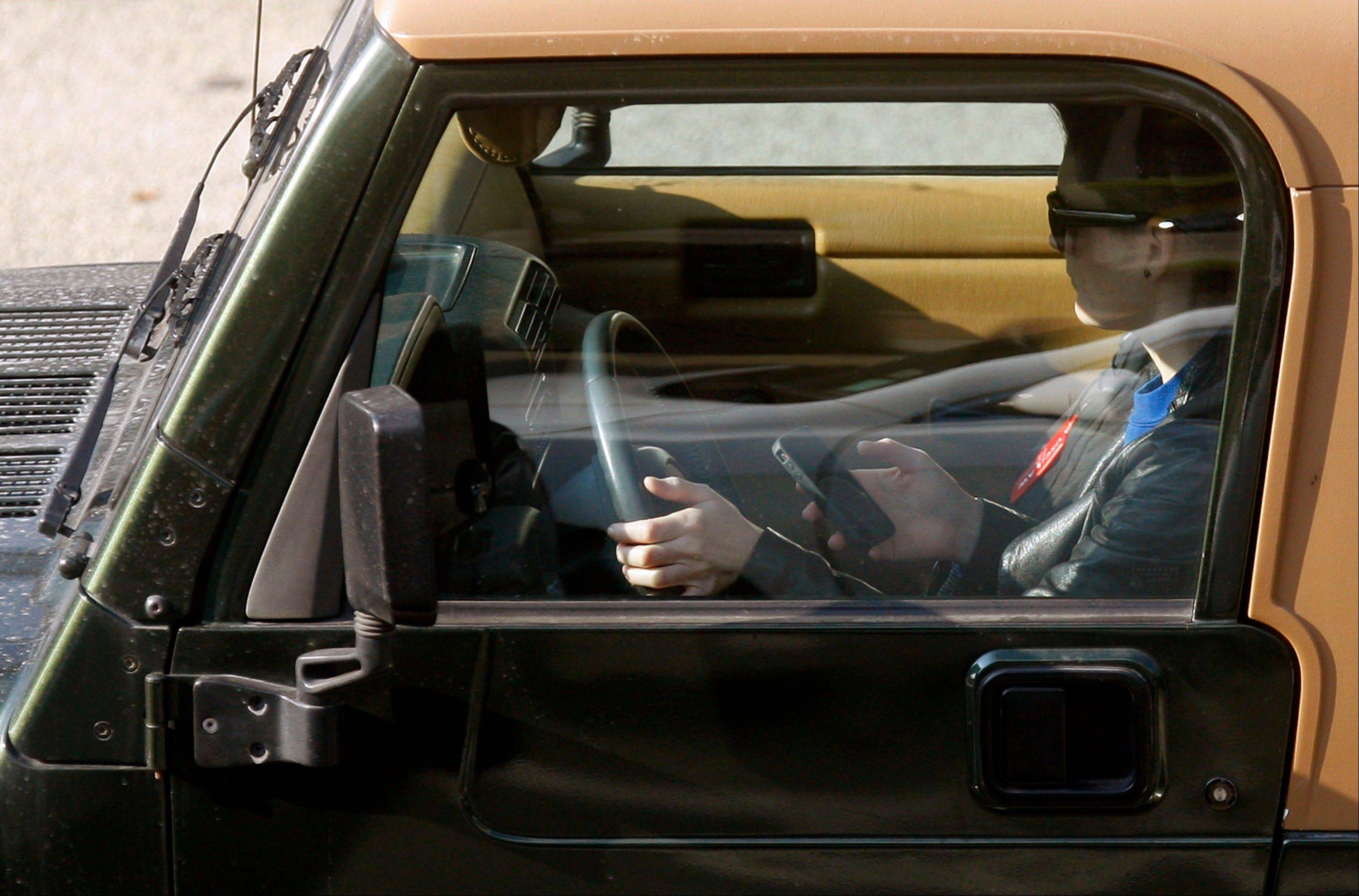 "A driver uses an iPhone while driving Wednesday, in Los Angeles. The country's four biggest cellphone companies are set to launch their first joint advertising campaign against texting while driving, uniting behind AT&T's ""It Can Wait"" slogan to blanket TV and radio during the summer of 2013."