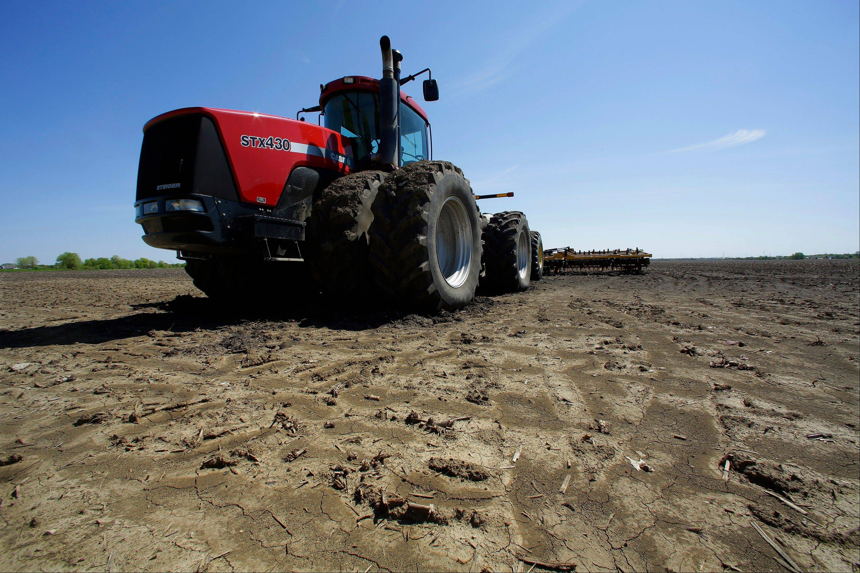 A tractor with cultivator sits idle after being delayed by wet weather earlier this month preventing central Illinois farmers from starting their spring planting of corn crops Monday.