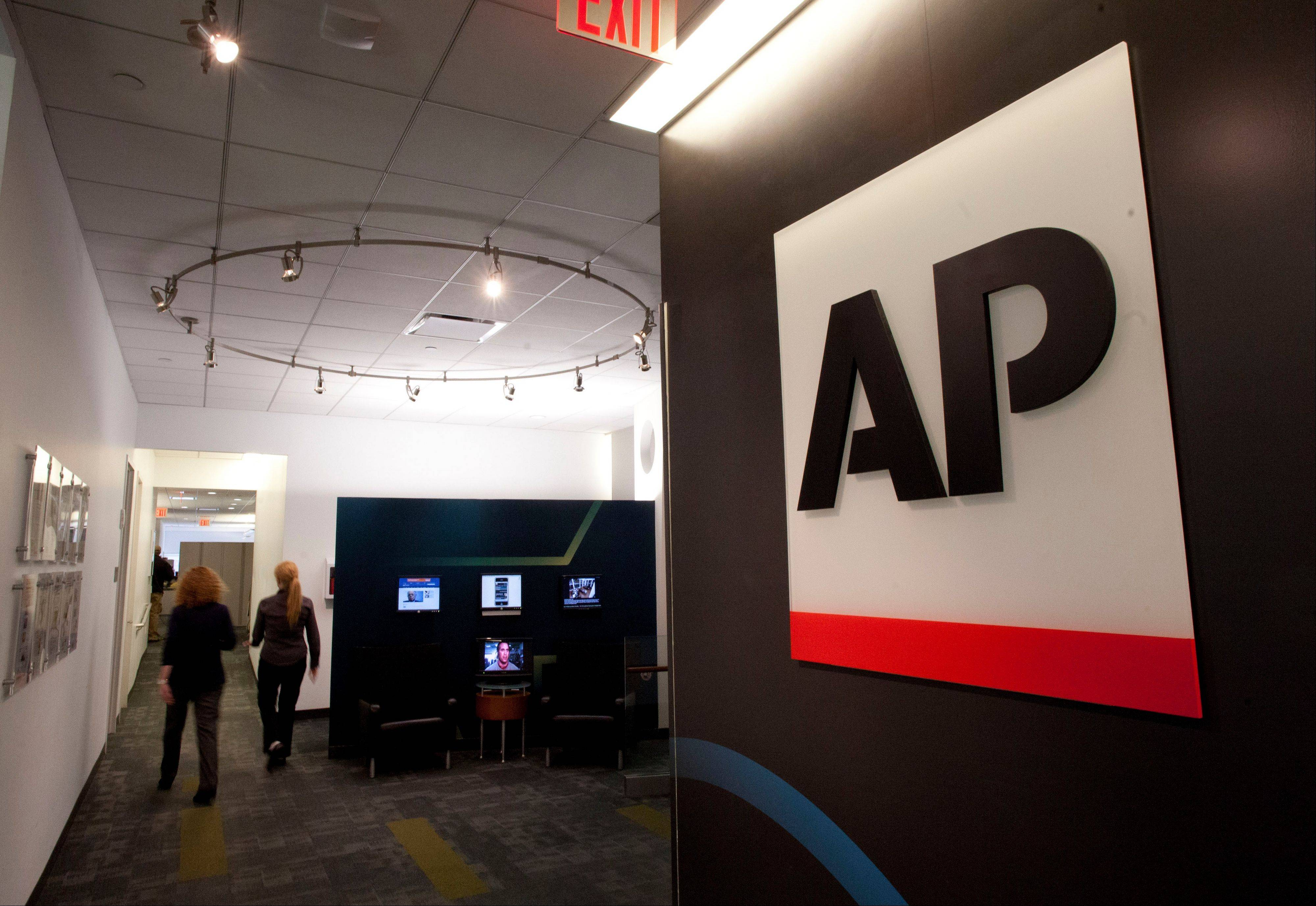 "Editorial employees walk through the headquarters of The Associated Press in New York Tuesday. The Justice Department secretly obtained telephone records from April and May 2012 of reporters and editors for the AP in what the news cooperative's top executive called a ""massive and unprecedented intrusion"" into how news organizations gather the news."