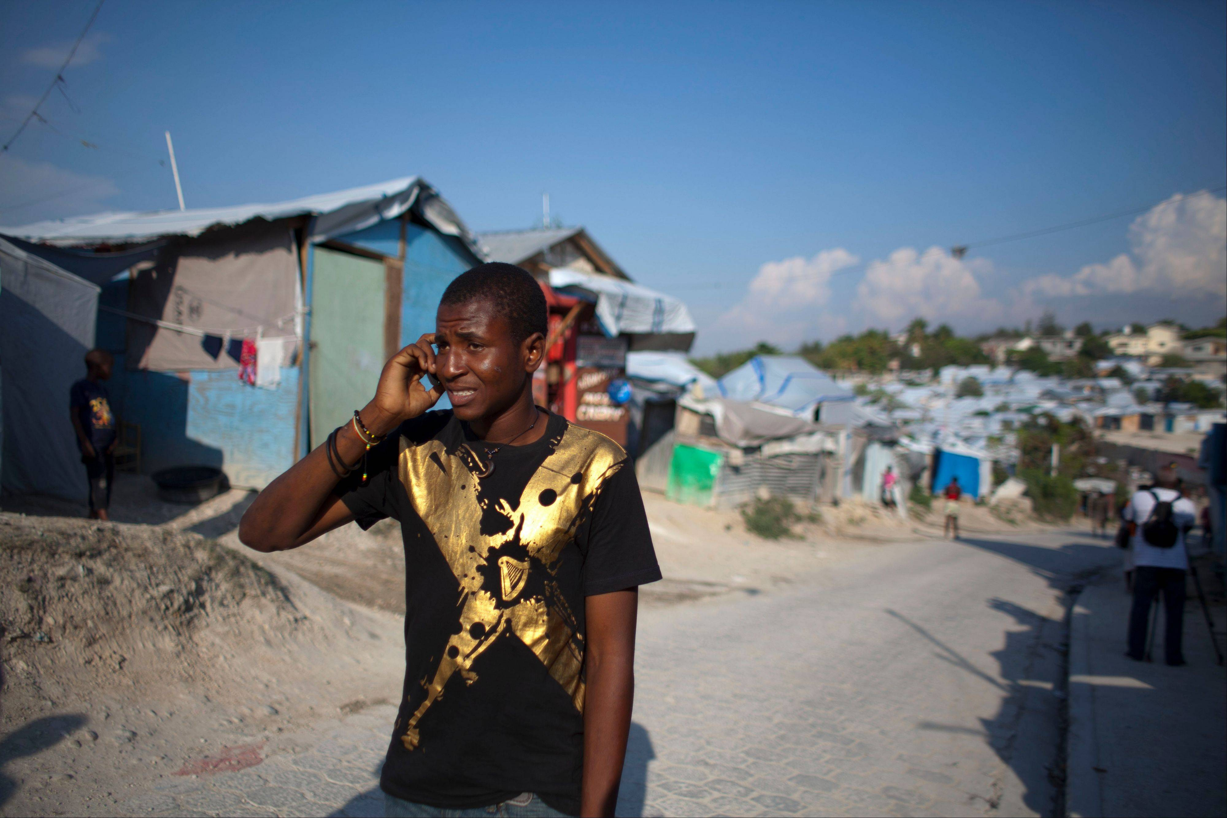 Darlin Lexima walks through Camp Acra in Port-au-Prince, Haiti. Lexima, 21, who lives in the camp for people displaced by the 2010 earthquake, was arrested by police early April 15 when he was walking home from a disco club as police were responding to residents protesting an earlier raid by an unidentified band of motorcyclist who set fire to their homes. In the few weeks since the mid-April confrontation, it has become an instant symbol for what many say is the growing use of threats and sometimes outright violence to clear out sprawling displaced person camps, where some 320,000 people still live.