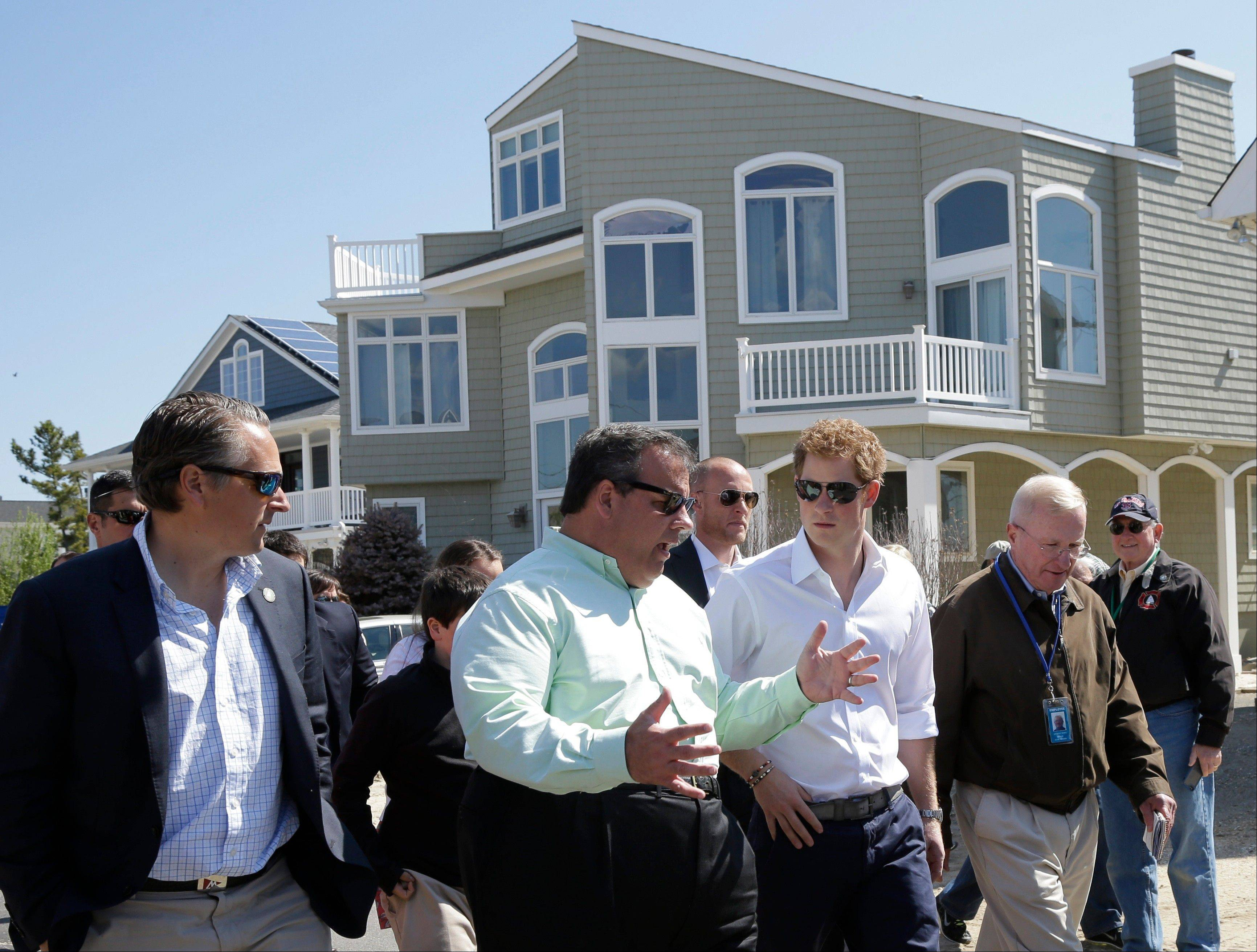 New Jersey Gov. Chris Christie, center left, walks with Britain's Prince Harry, center, while visiting the area hit by Superstorm Sandy, Tuesday, May 14, 2013, in Seaside Heights, N.J.