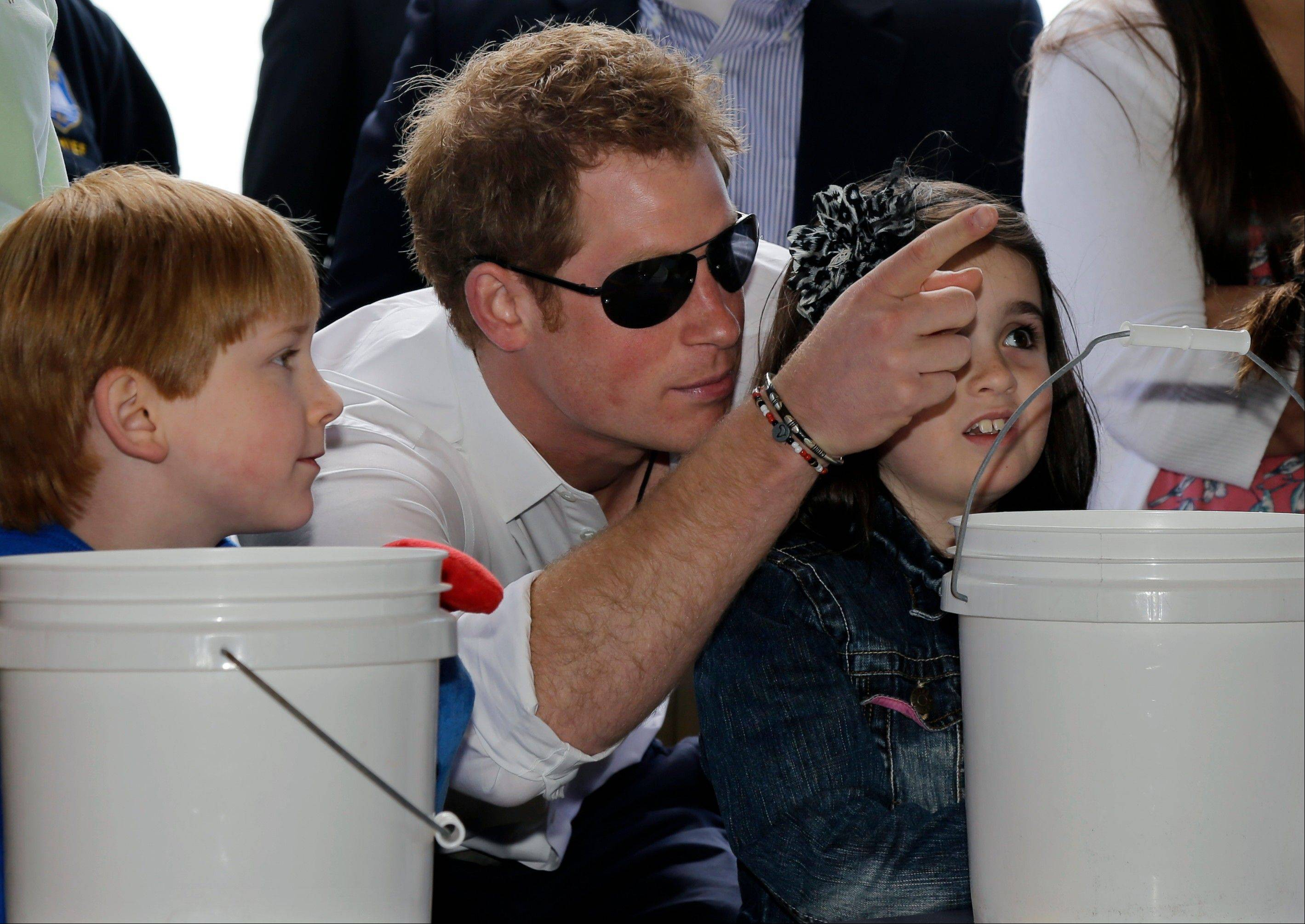 Michael Vanover, 7, left, looks on as Britain's Prince Harry helps Taylor Cirigliano, 11, right, pick a prize at a Ball Toss game on the boardwalk, while visiting the area hit by Superstorm Sandy, Tuesday, May 14, 2013, in Seaside Heights, N.J.
