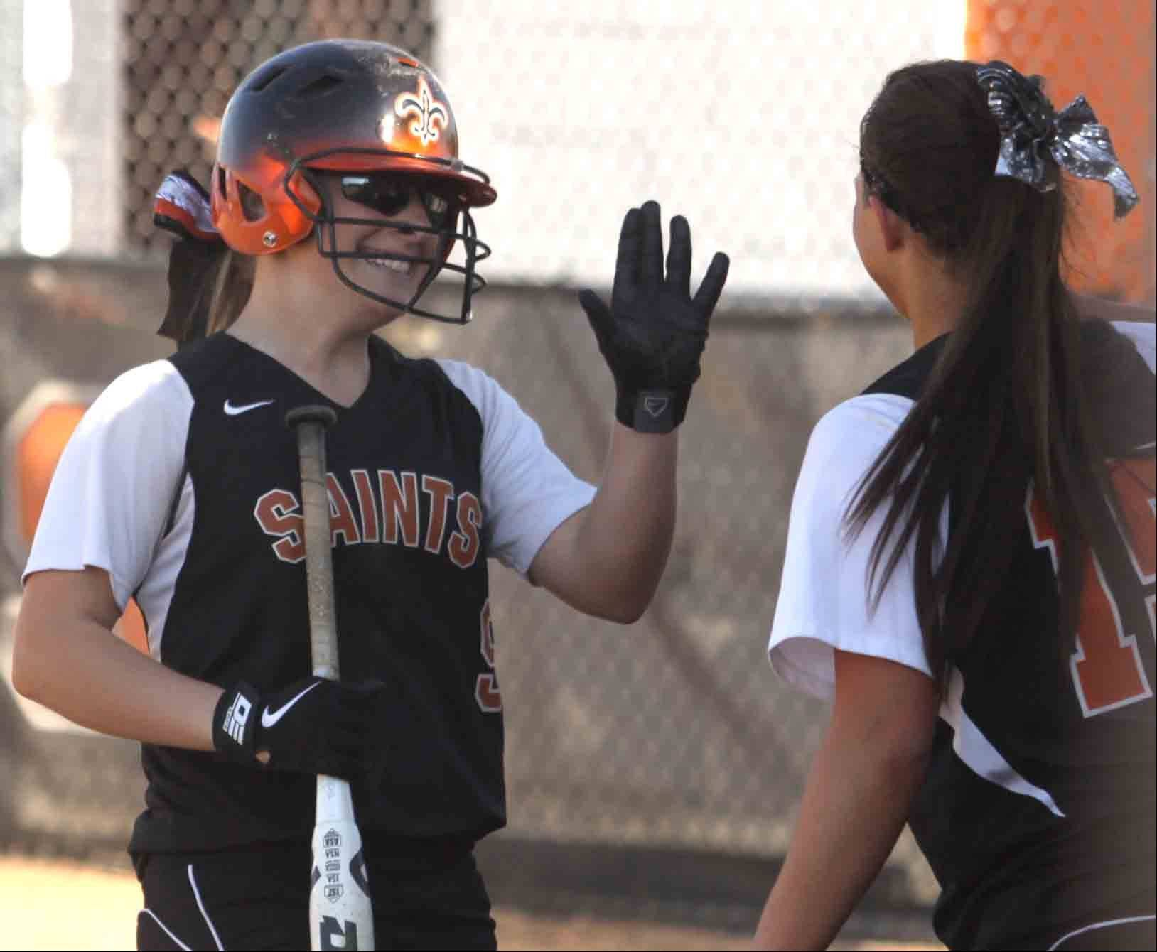 St Charles East's Sarah Collalti, left, is all smiles after coming around to score. Greeting her is teammate Alex Latoria as they played St Charles North in a varsity softball game at St Charles East on Tuesday afternoon.