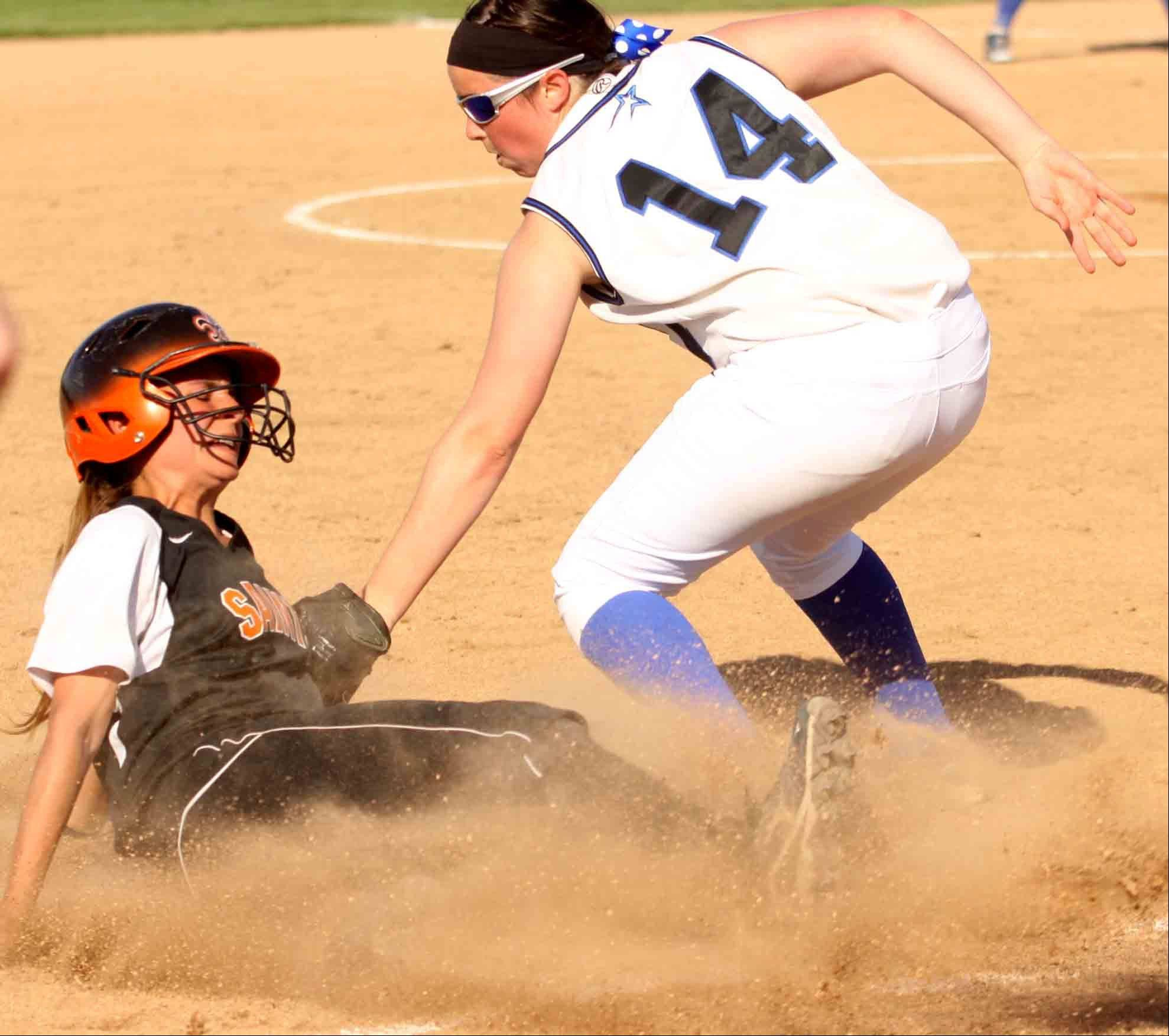 St Charles East's Lexi Perez slides in safe at third base as St Charles North's Erin Nemitz applies the tag during a varsity softball game at St Charles East on Tuesday afternoon.