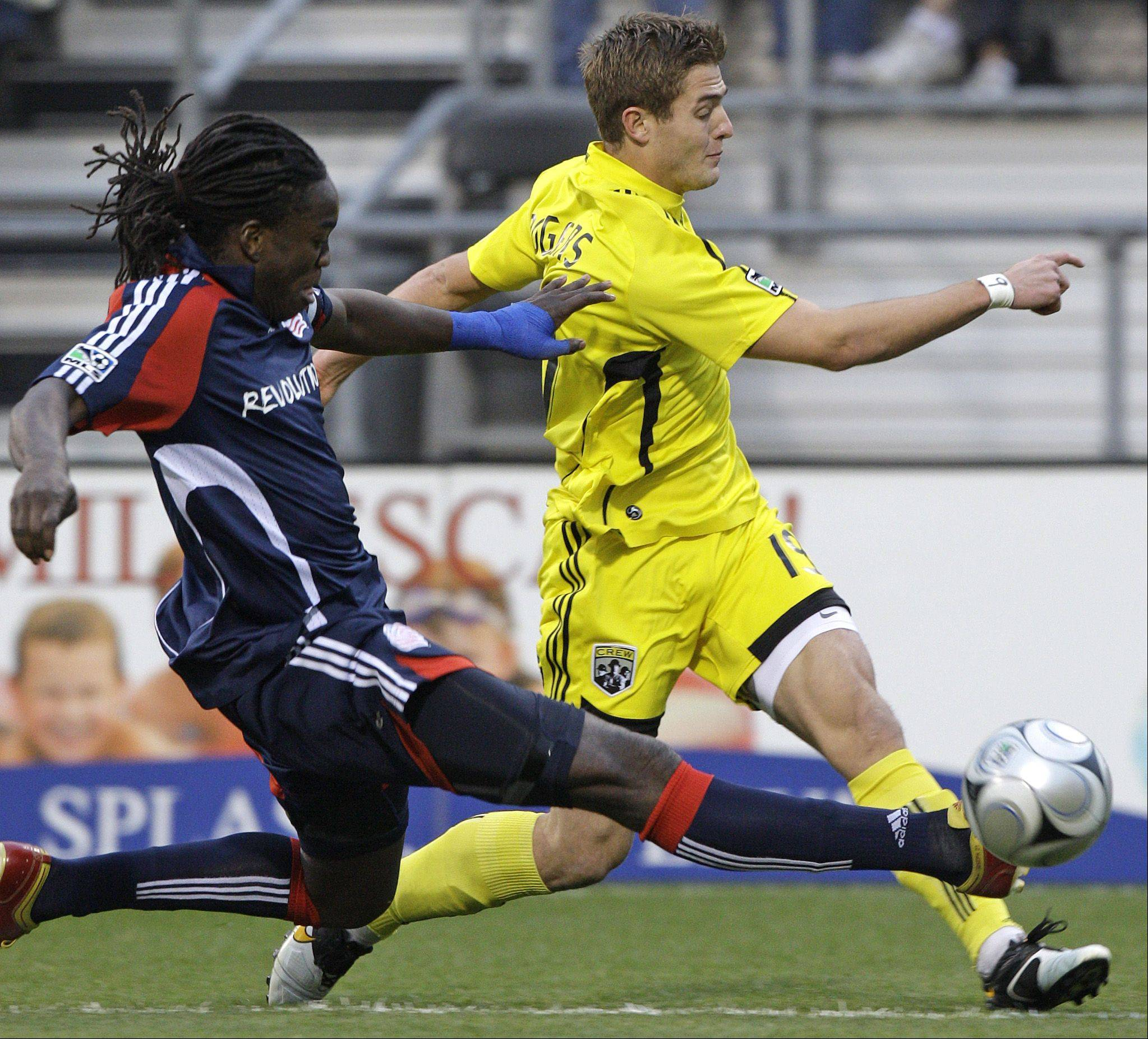 New England Revolution's Shalrie Joseph, left, tries to clear the ball past Columbus Crew's Robbie Rogers during the first half of an MLS soccer game Sunday, Oct. 25, 2009, in Columbus, Ohio.