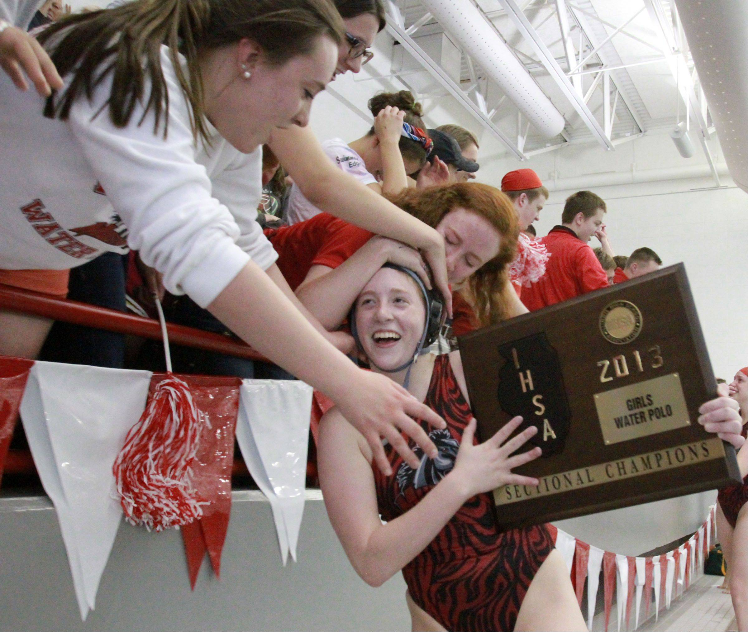 Mundelein's Allie Boothe holds the girls water polo sectional plaque and gets hugs from her sister Amanda, far left, and friend Megan Casali Saturday. Mundelein defeated Stevenson in the match.