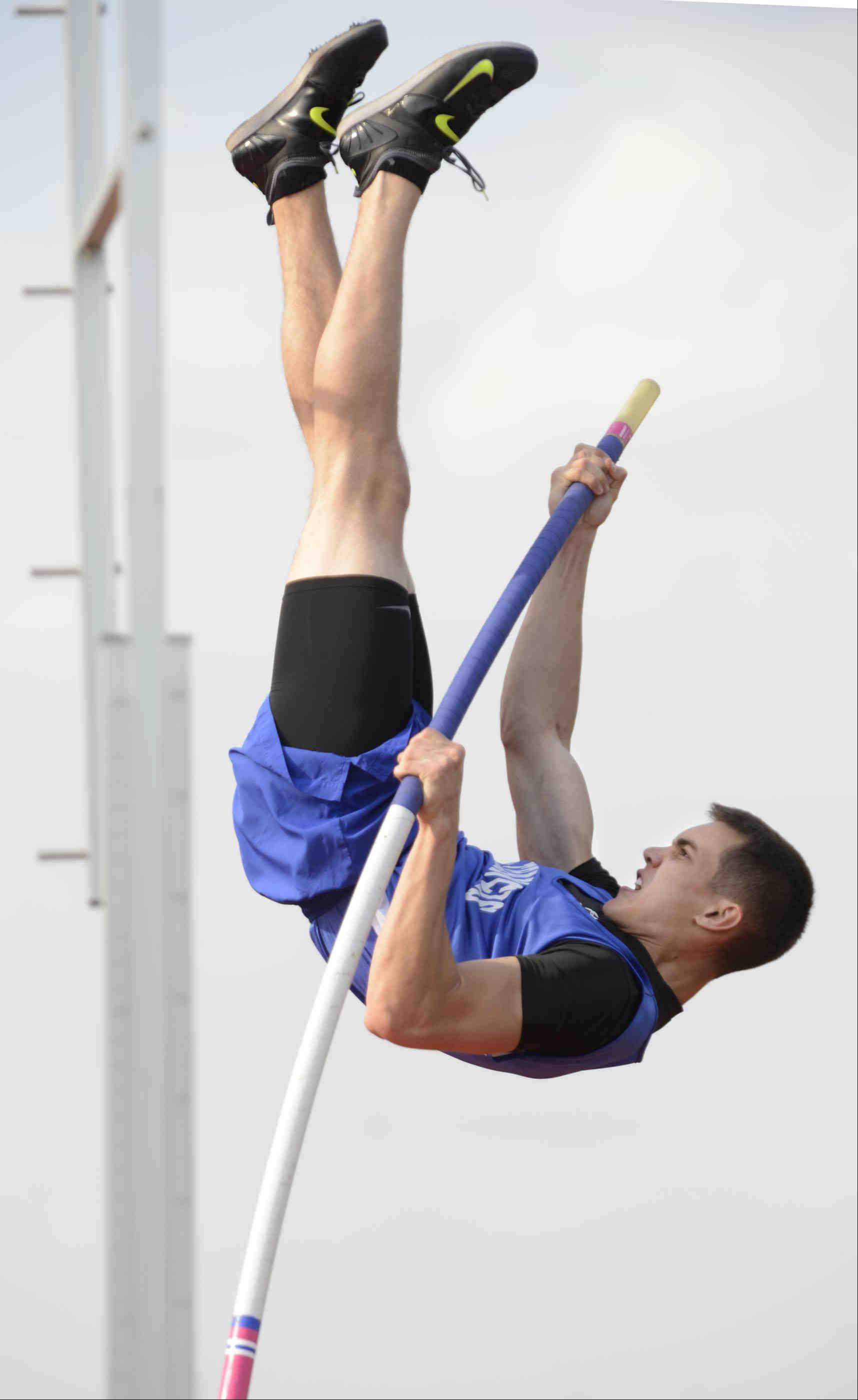Wheaton St. Francis pole vaulter Micheal Wilson pulls his way to the bar Wednesday in Aurora.