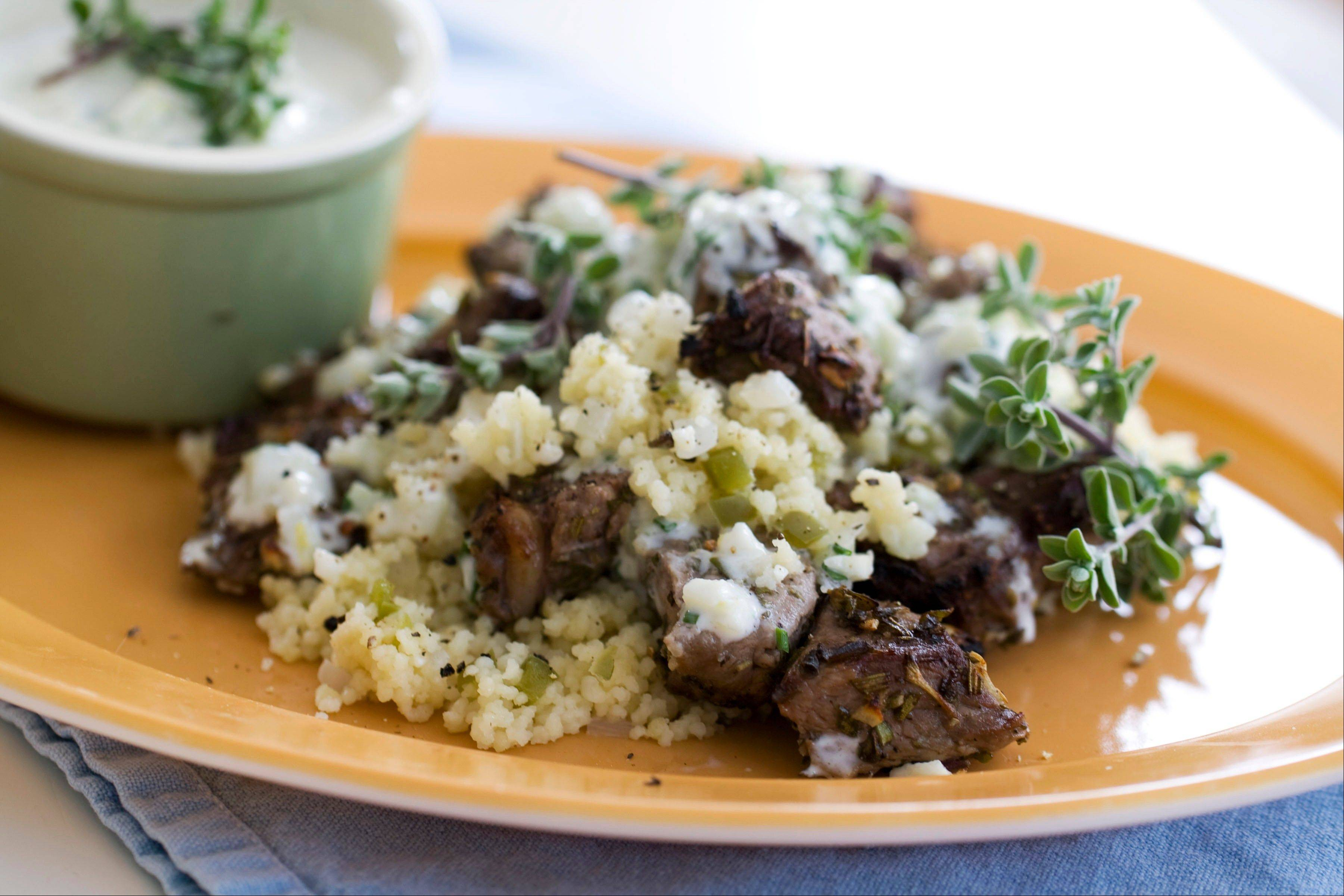 Lemon zest and garlic make a flavorful rub for lamb kebabs. Serve them on a bed of bell pepper couscous.