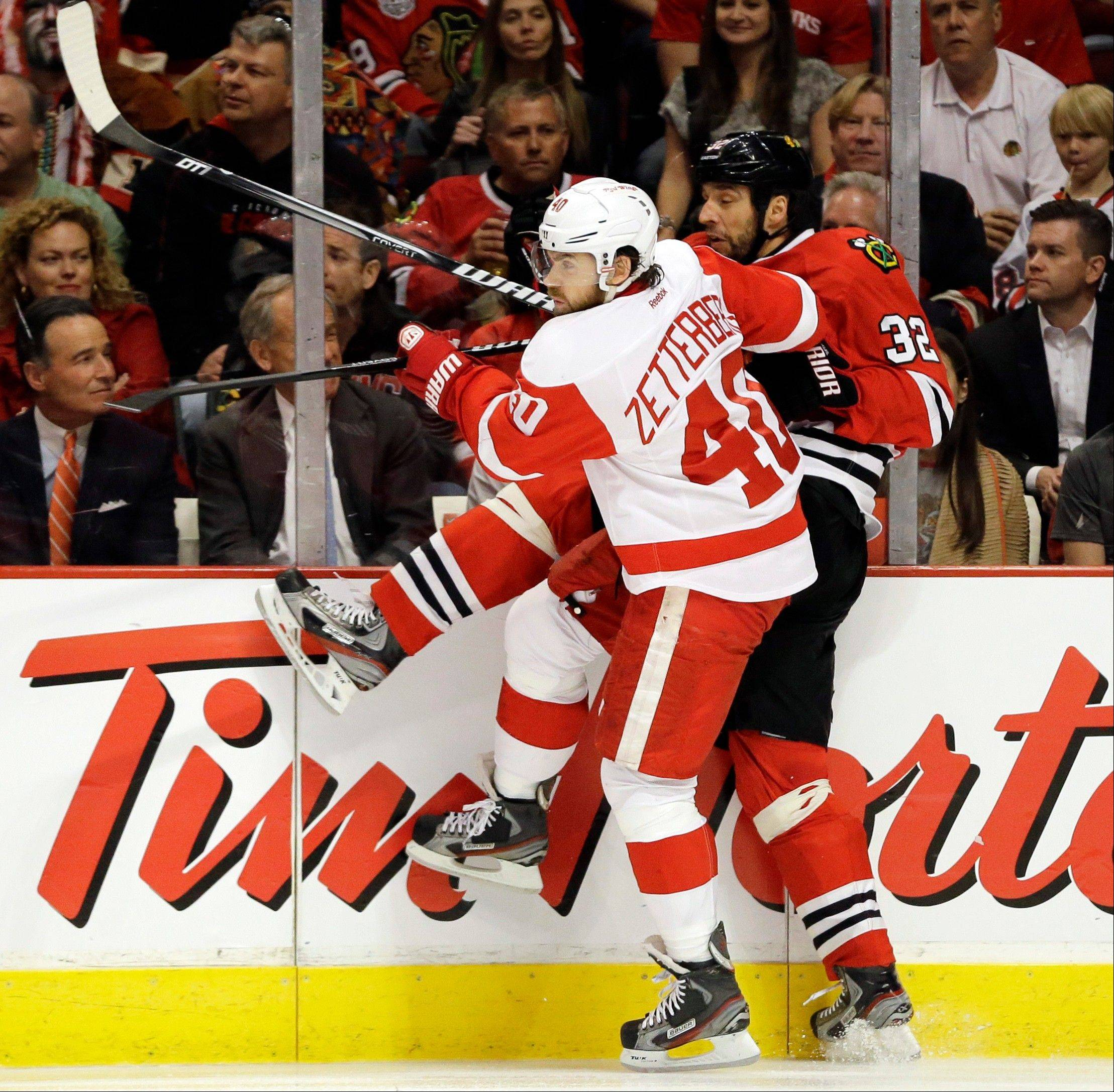 The Hawks� Michal Rozsival (32) is checked by Detroit Red Wings� Henrik Zetterberg (40) during the first period of Game 1 of an NHL hockey playoffs Western Conference semifinal in Chicago, Wednesday, May 15, 2013. (AP Photo/Nam Y. Huh)