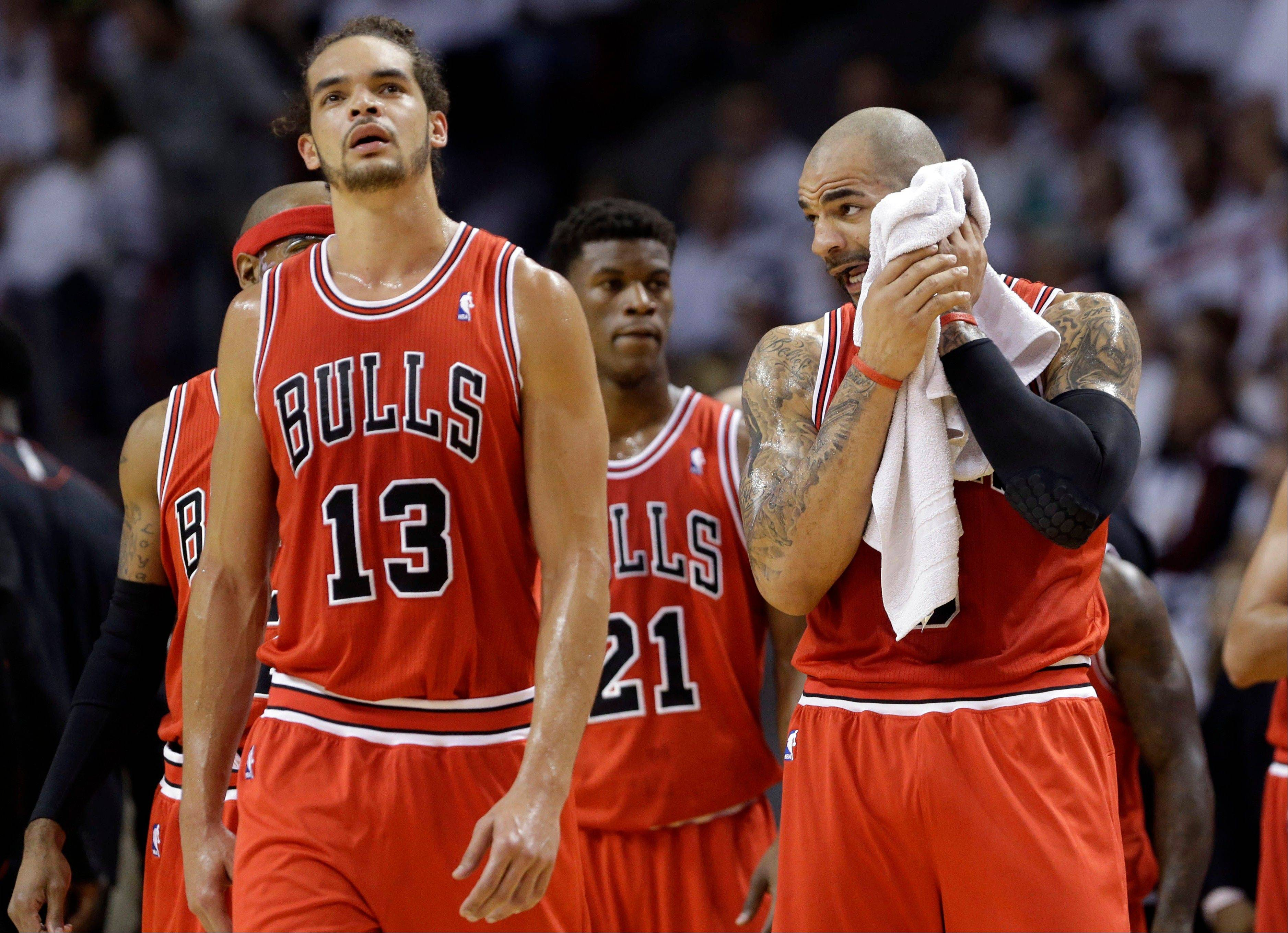 Chicago Bulls' Carlos Boozer wipes his face as he stands with Joakim Noah (13) during a time out in the first half against the Miami Heat in Game 5 of an NBA basketball Eastern Conference semifinal, Wednesday, May 15, 2013, in Miami.