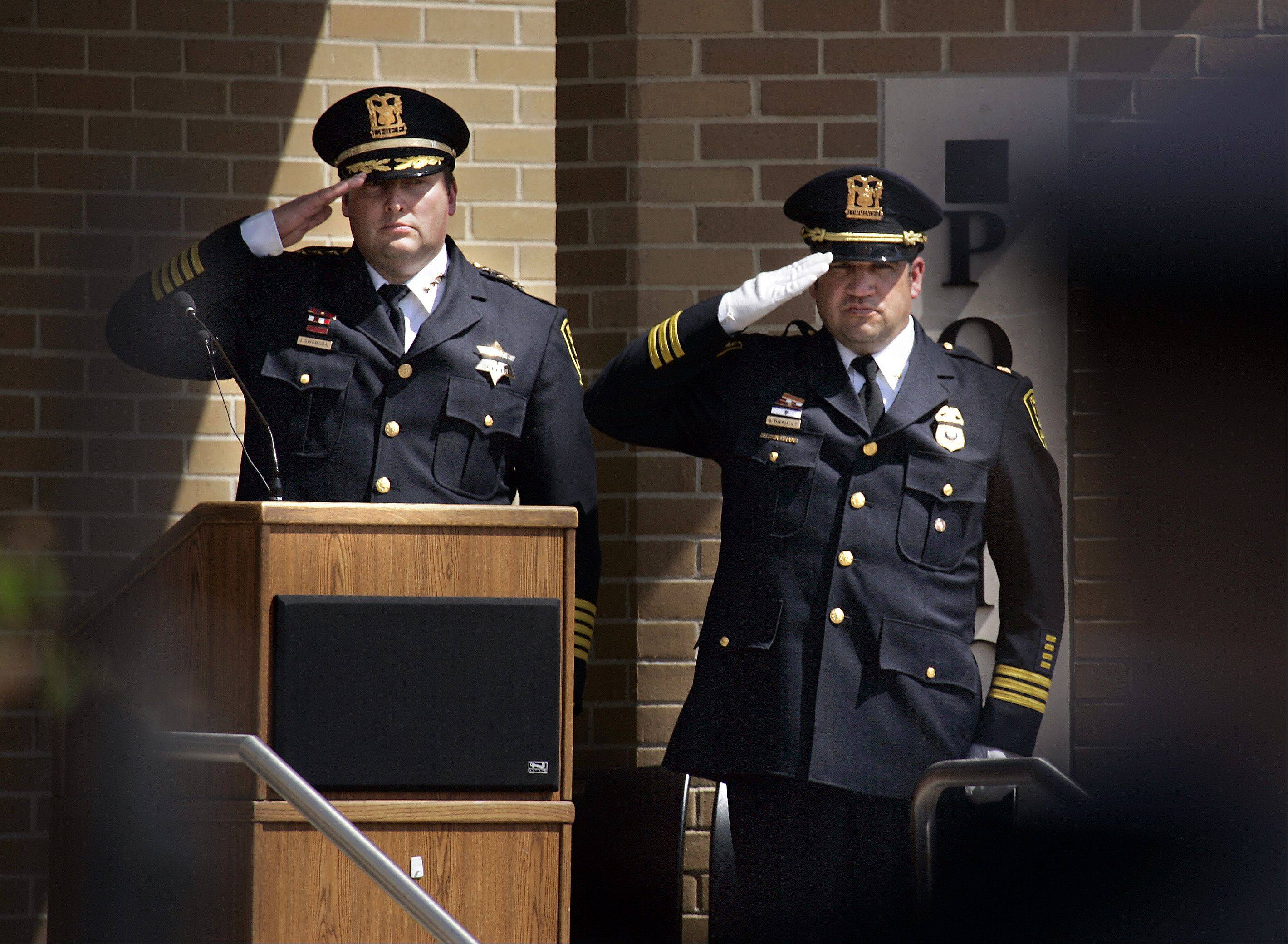 Elgin Police Chief Jeff Swoboda, left, and Cmdr. Glenn Theriault salute the colors during Wednesday's Elgin Police Department memorial service.