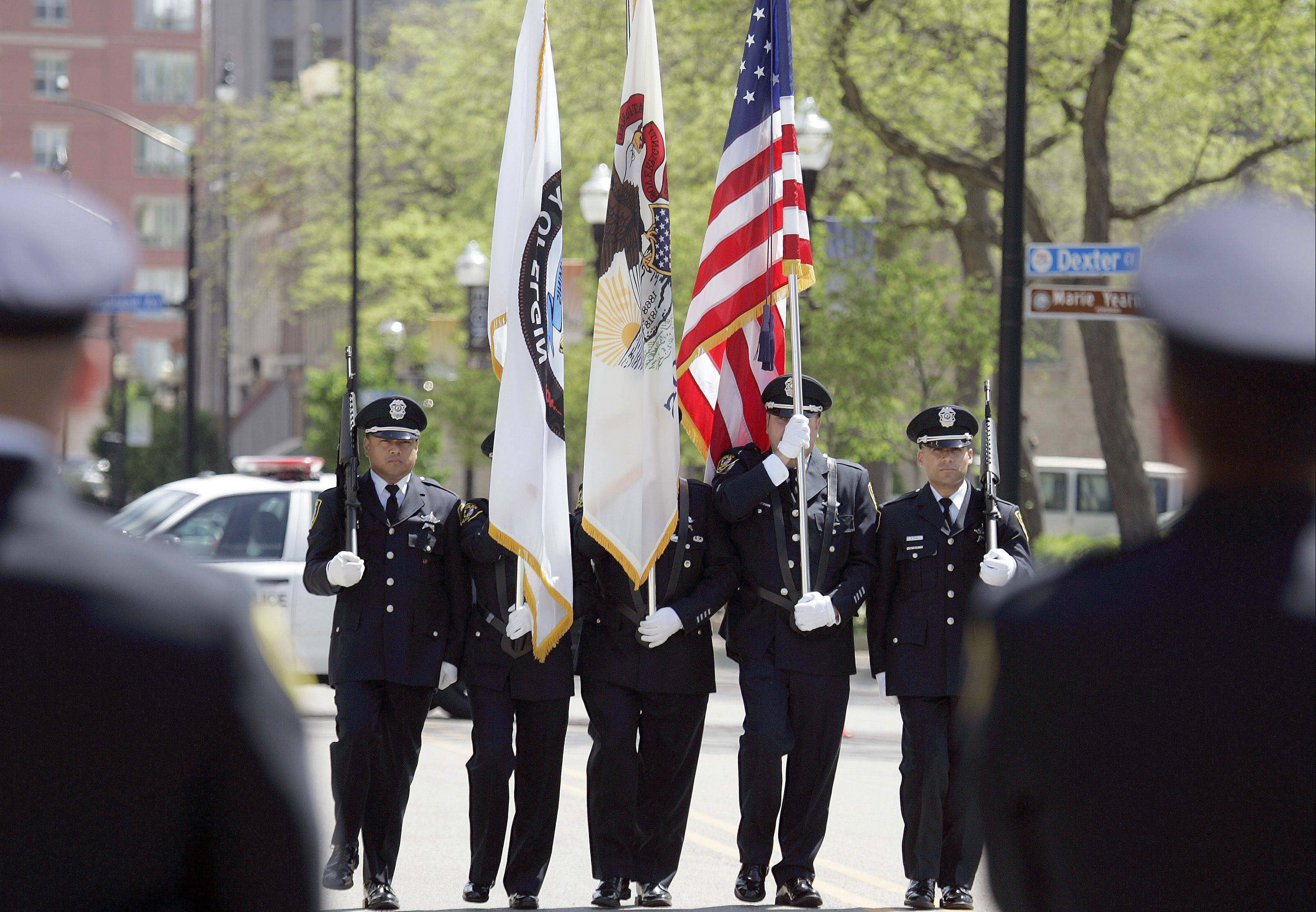 Framed by their fellow officers, the honor guard moves along Douglas Avenue in presenting the colors at the beginning of Wednesday's Elgin Police Department memorial service.
