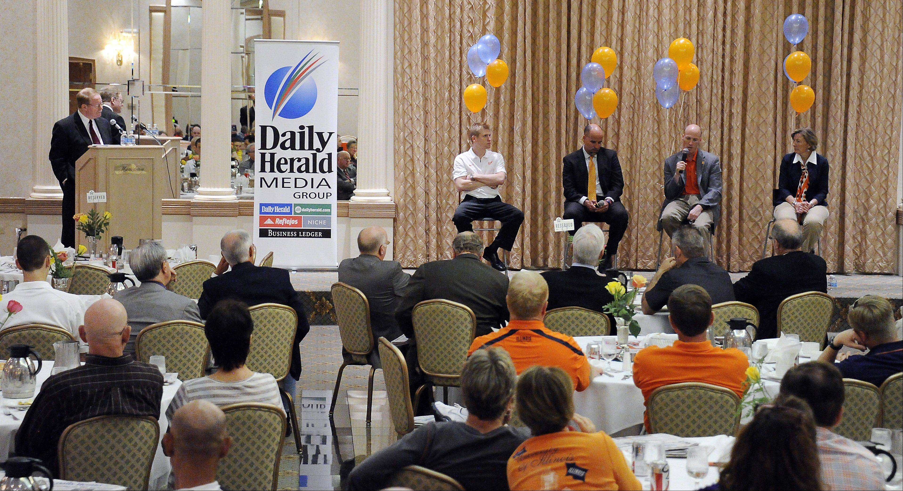 University of Illinois coaches Justin Spring (men's gymnastics), Matt Bollant (women's basketball), John Groce (men's basketball), and Janet Rayfield (women's soccer) answer questions at the Illini Caravan event Wednesday in Rolling Meadows.