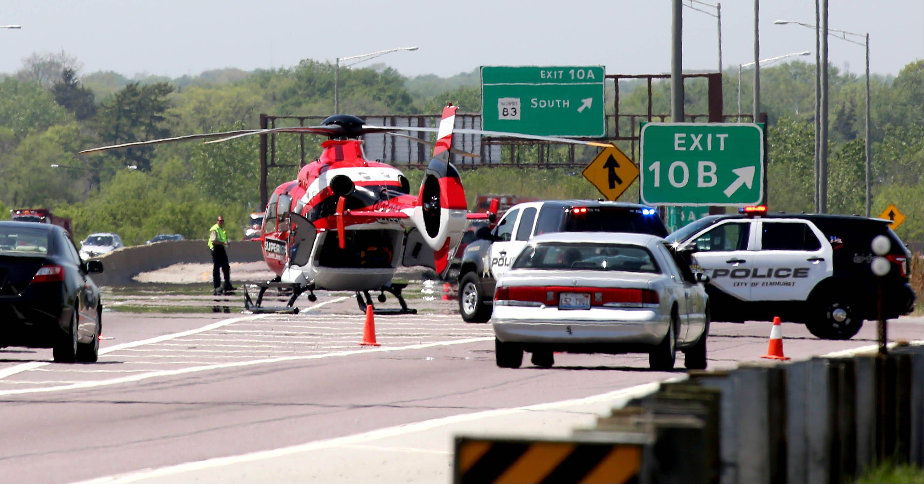 A medical helicopter lands Wednesday on I-290 at Route 83 after a semitrailer truck overturned and trapped the driver inside.