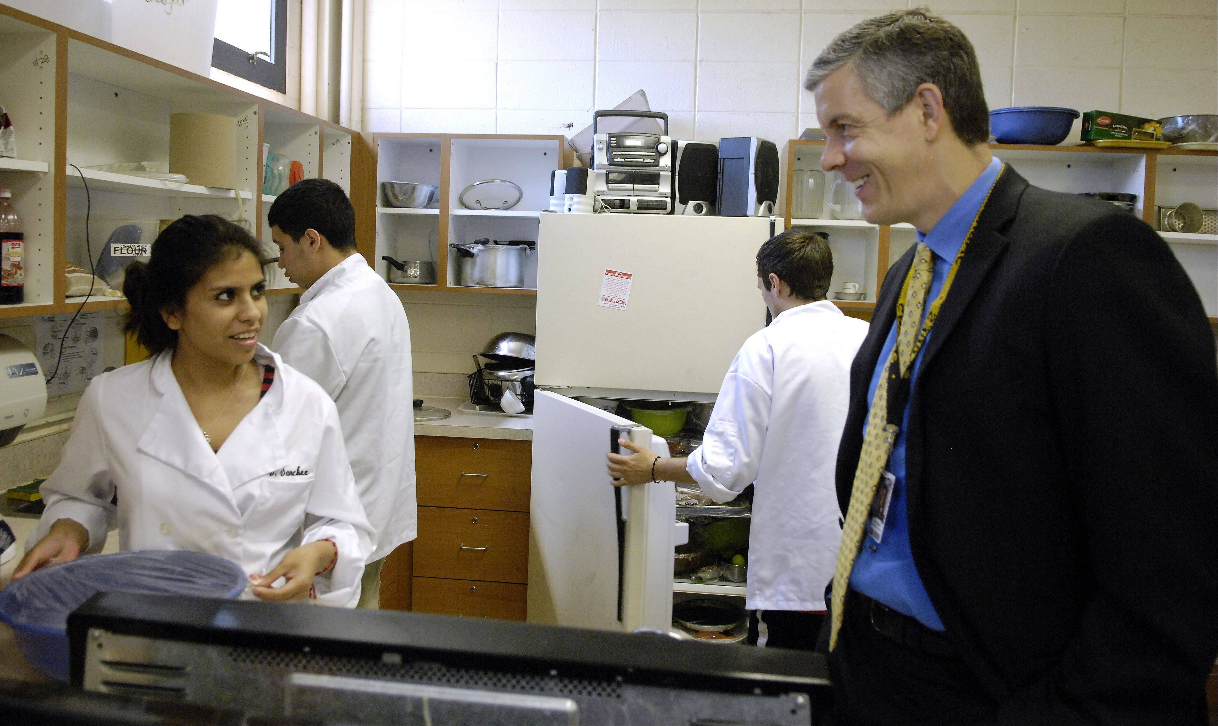 U.S. Secretary of Education Arne Duncan talks with junior Suset Sanchez in her culinary arts class during a visit to Streamwood High School Wednesday.