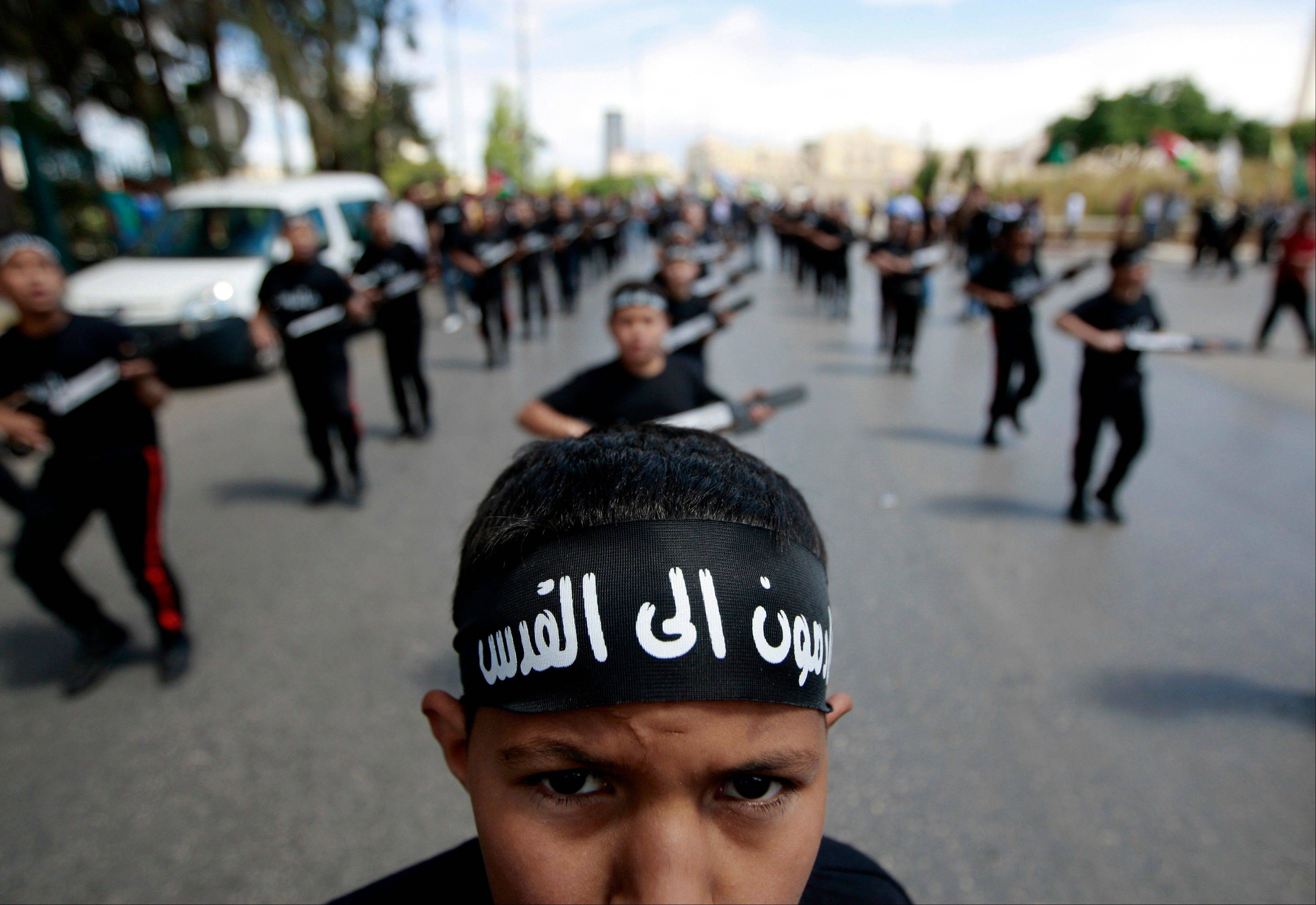 "A Palestinian boy wears a bandanna which in Arabic that reads, ""coming to Jerusalem,"" during a rally to mark the Nakba Day in the West Bank town of Rramallah, Wednesday, May 15, 2013., Tuesday, May 14, 2013."