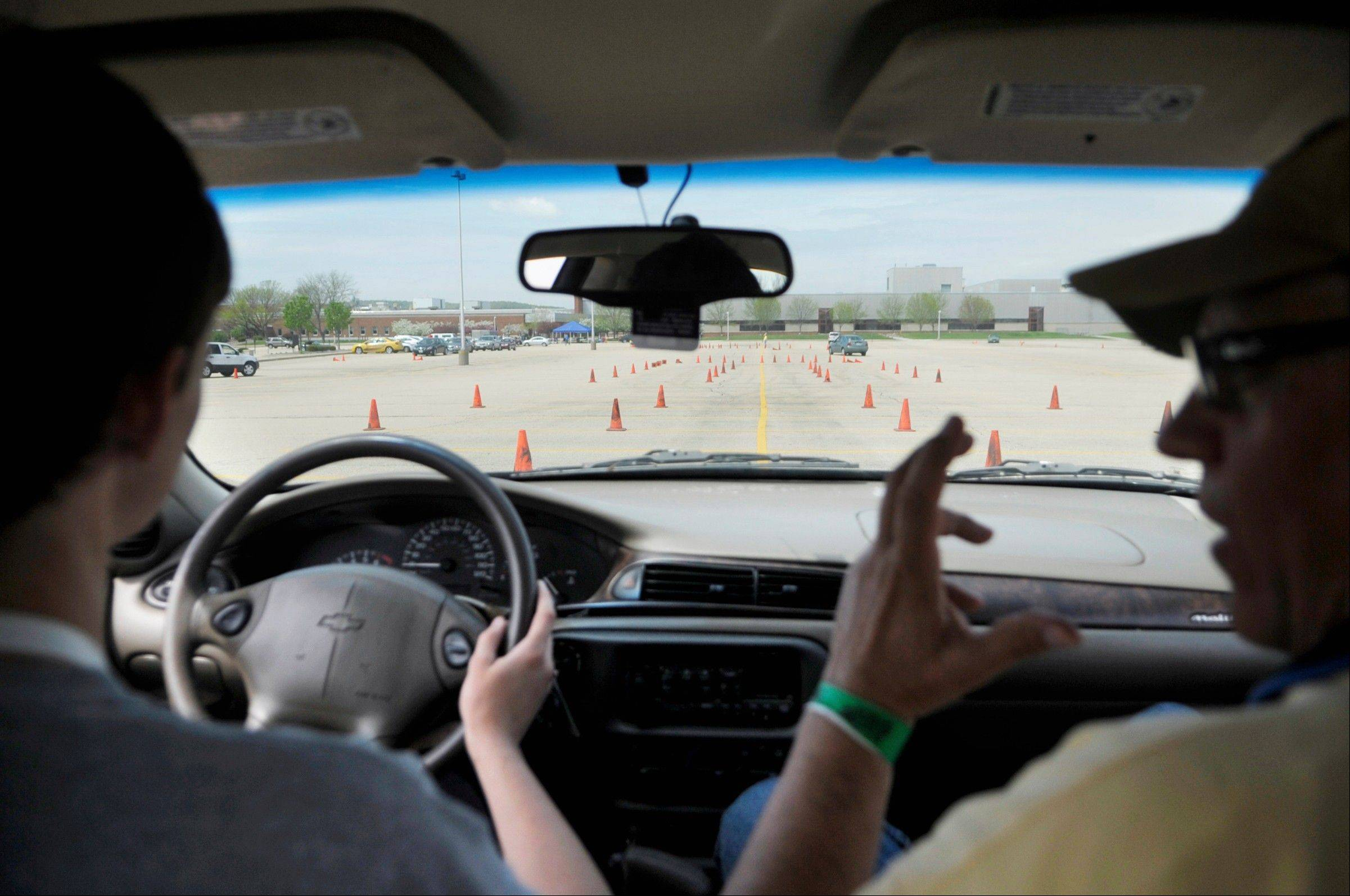 Colin Flaherty, 17, of Peoria talks with driving instructor Steve Smart, right, before maneuvering his car through cones at the Tire Rack Street Survival teen driving program at Caterpillar's Mossville plant.