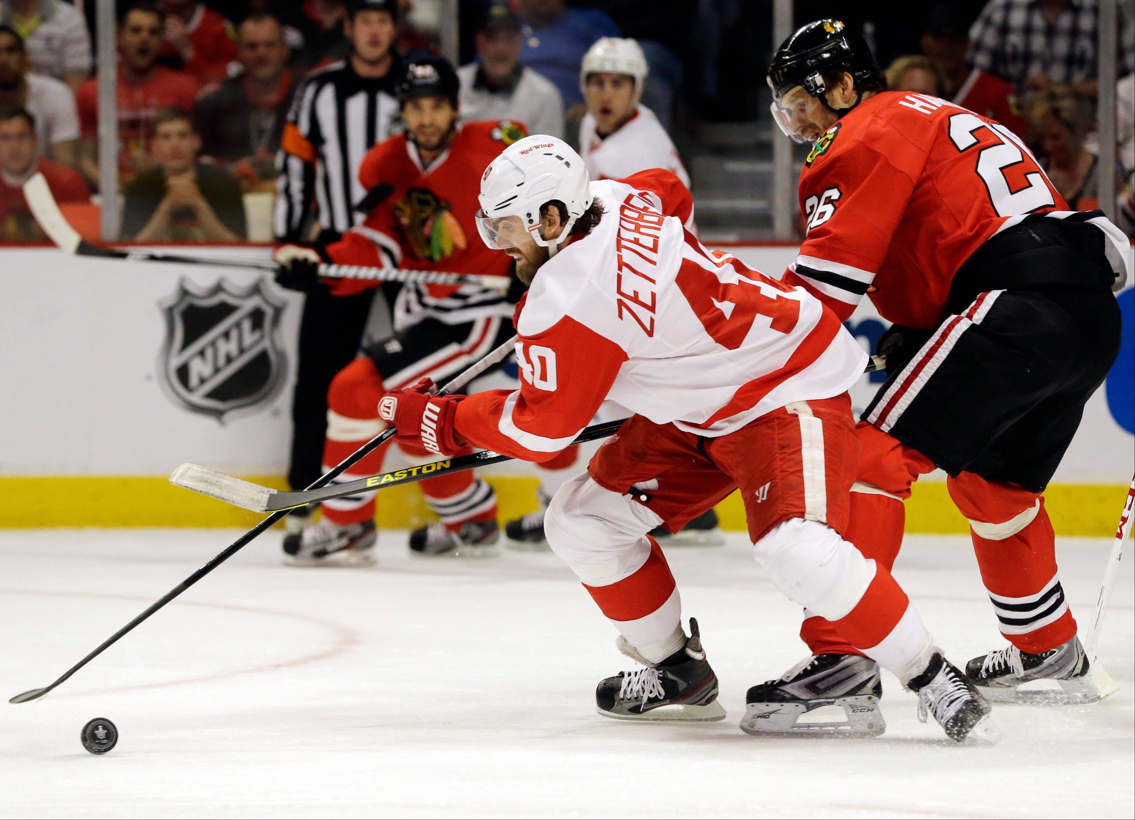 Detroit Red Wings' Henrik Zetterberg (40) controls the puck against Chicago Blackhawks' Michal Handzus (26) during the first period of Game 1 of an NHL hockey playoffs Western Conference semifinal in Chicago, Wednesday, May 15, 2013.