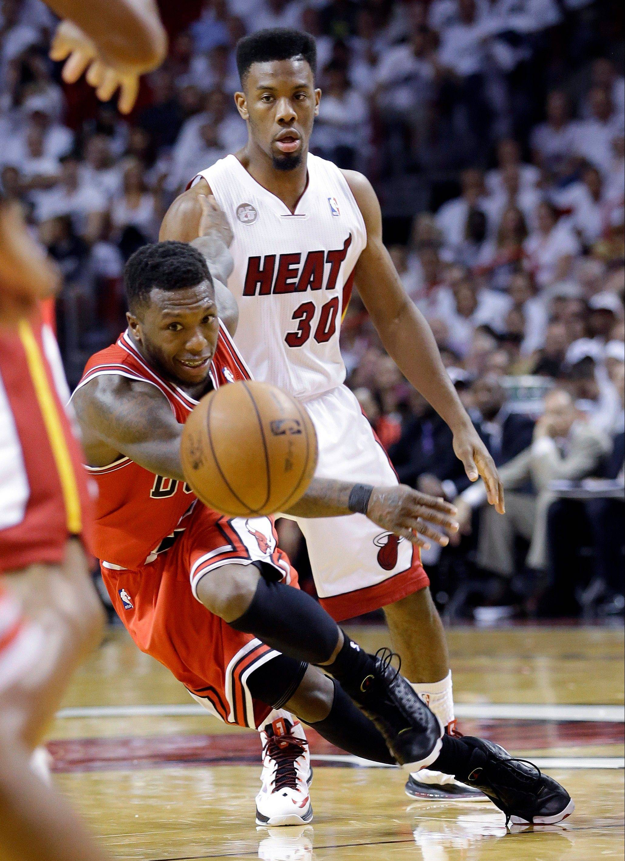 Nate Robinson passes the ball as Miami's Norris Cole watches during the second half of the Bulls' loss Wednesday.