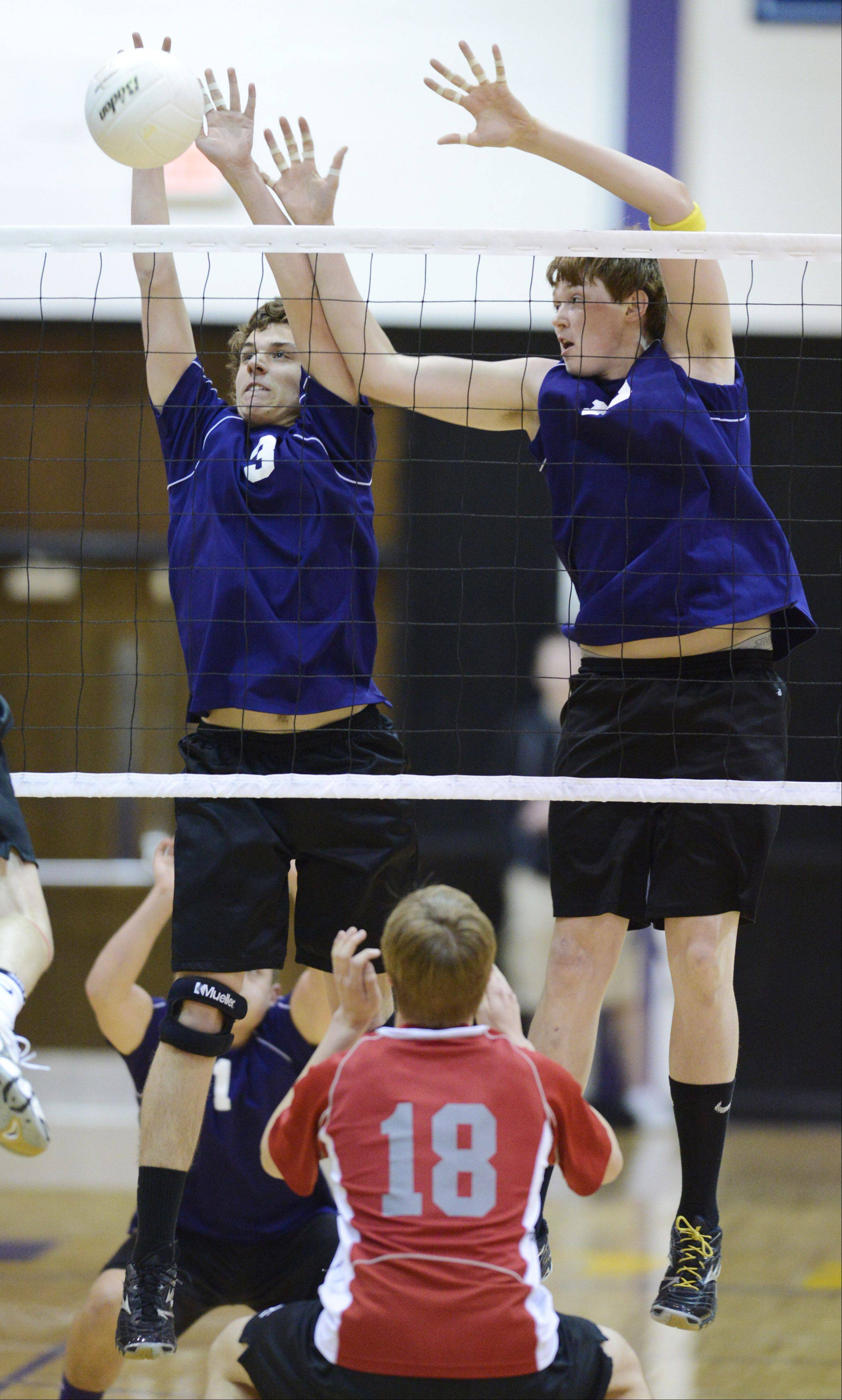 Rolling Meadows' Brett Frey, left, and Tim Ellis block the ball at the net during the Mid-Suburban League championship against Palatine on Wednesday.