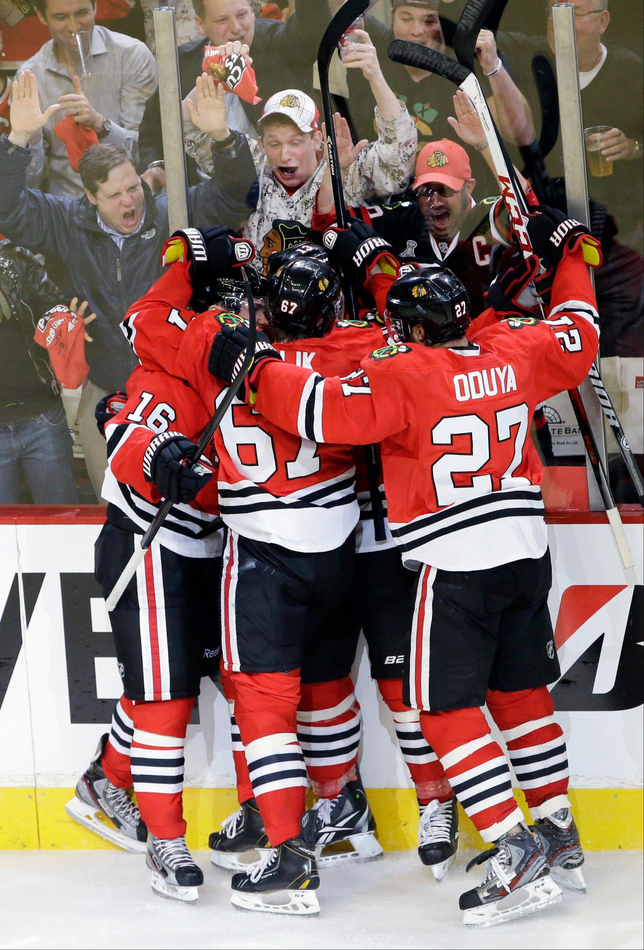 Chicago Blackhawks' Marcus Kruger (16), left, celebrates with teammates after scoring a goal during the third period of Game 1 of an NHL hockey playoffs Western Conference semifinal against the Detroit Red Wings Wednesday at the United Center.