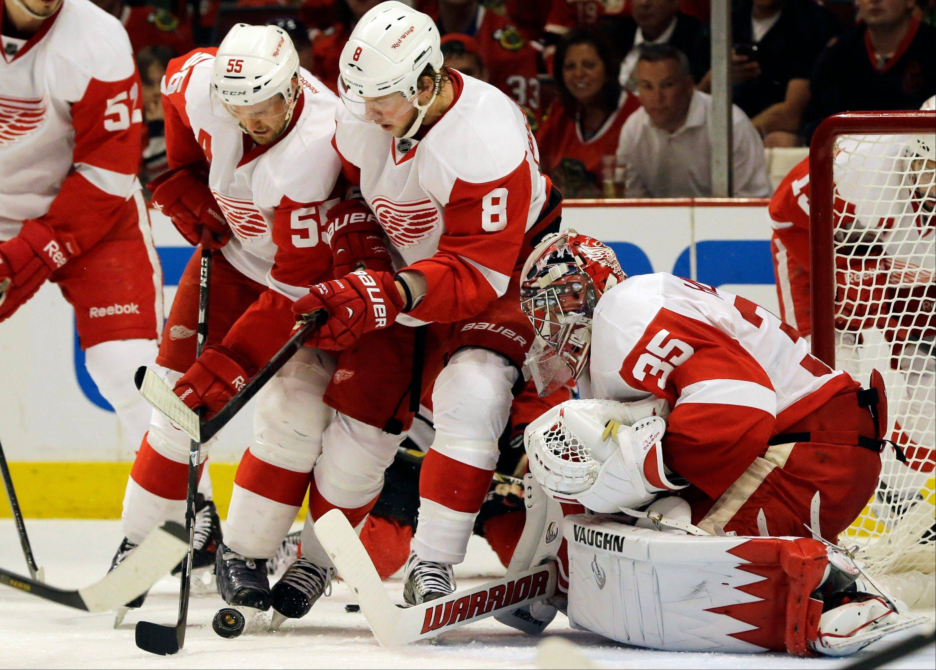 Detroit Red Wings goalie Jimmy Howard (35) blocks a shot as teammates Justin Abdelkader (8) and Niklas Kronwall (55) look on during the second period of Game 1 of an NHL hockey playoffs Western Conference semifinal against the Chicago Blackhawks in Chicago, Wednesday, May 15, 2013.