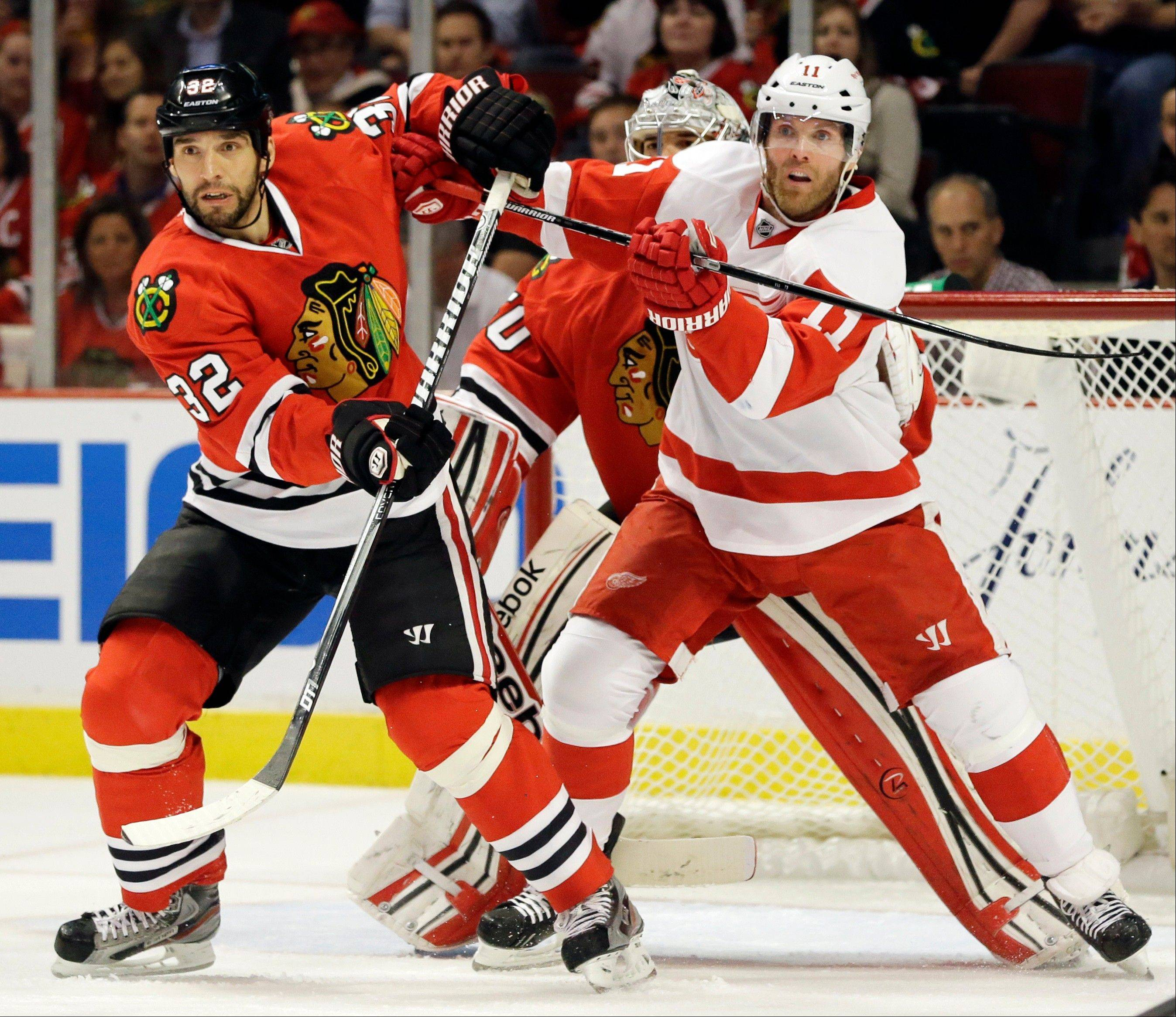 Detroit Red Wings' Daniel Cleary, right, and Chicago Blackhawks' Michal Rozsival battle as they wait for the puck during the first period of Game 1 of an NHL hockey playoffs Western Conference semifinal in Chicago, Wednesday, May 15, 2013.
