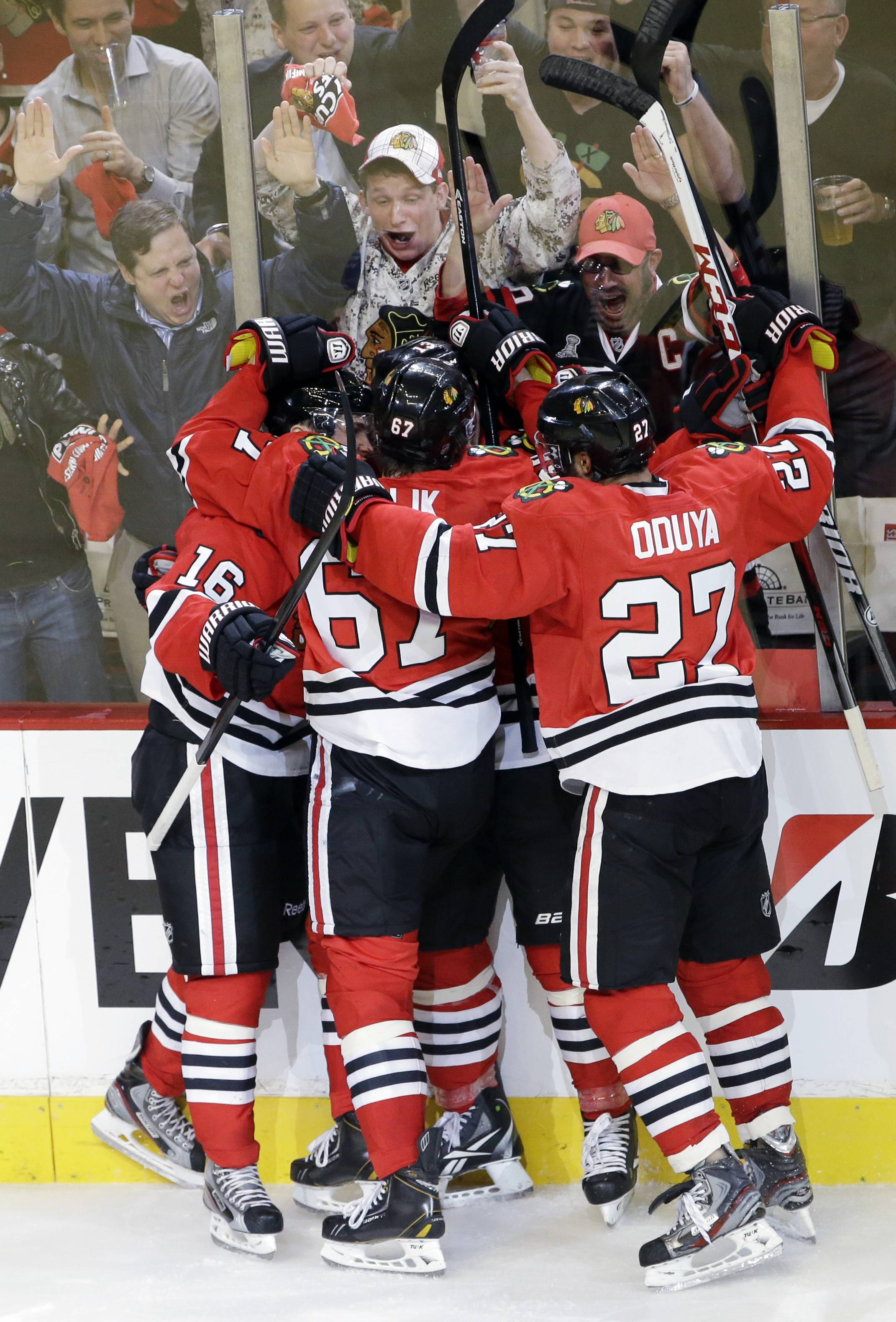 Chicago Blackhawks' Marcus Kruger (16), left, celebrates with teammates after scoring a goal during the third period of Game 1 of an NHL hockey playoffs Western Conference semifinal against the Detroit Red Wings in Chicago, Wednesday, May 15, 2013.