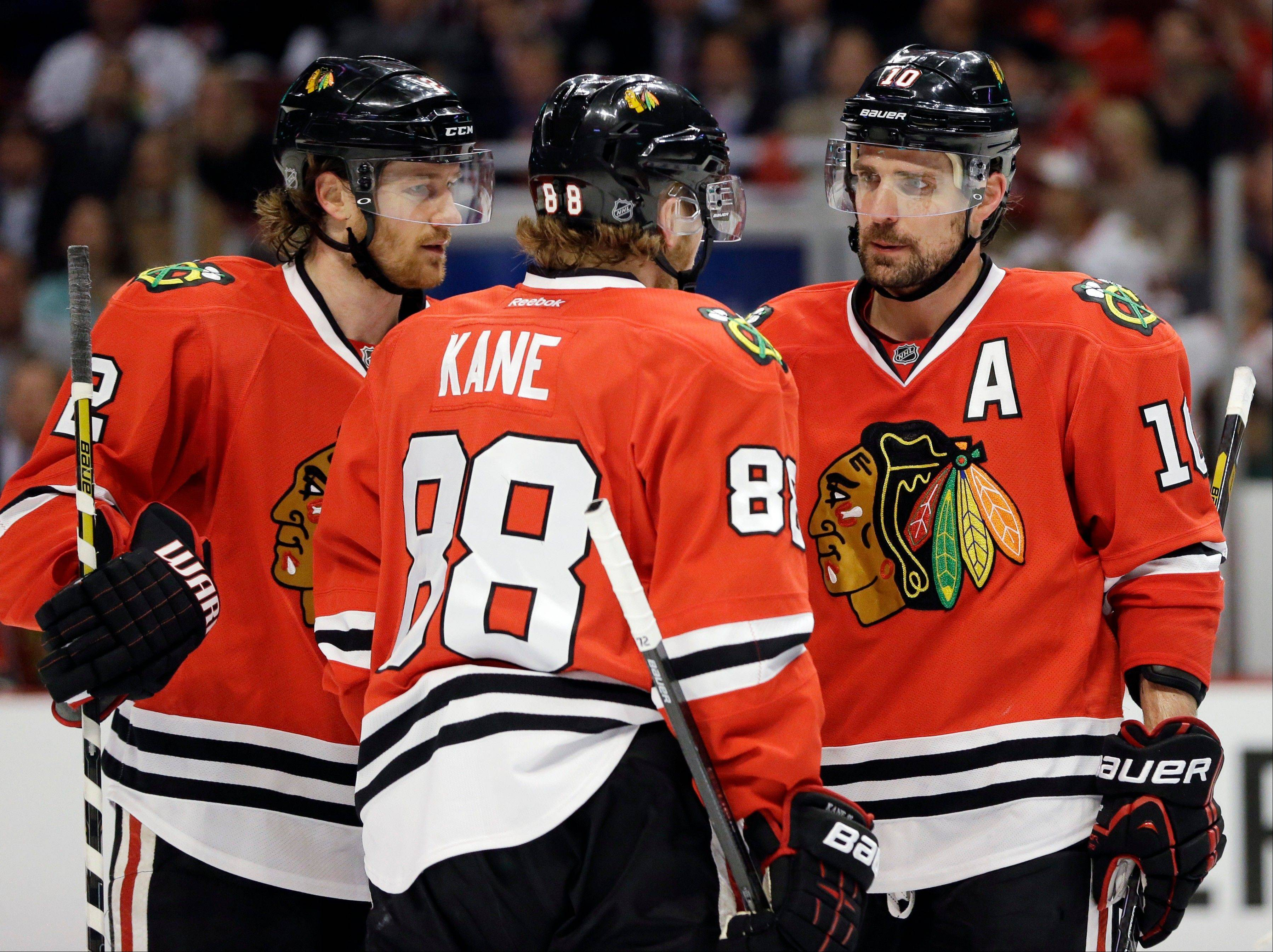 Chicago Blackhawks' Patrick Sharp (10) talks with teammates Duncan Keith (2) and Patrick Kane (88) during the second period of Game 1 of an NHL hockey playoffs Western Conference semifinal against the Detroit Red Wings in Chicago, Wednesday, May 15, 2013.